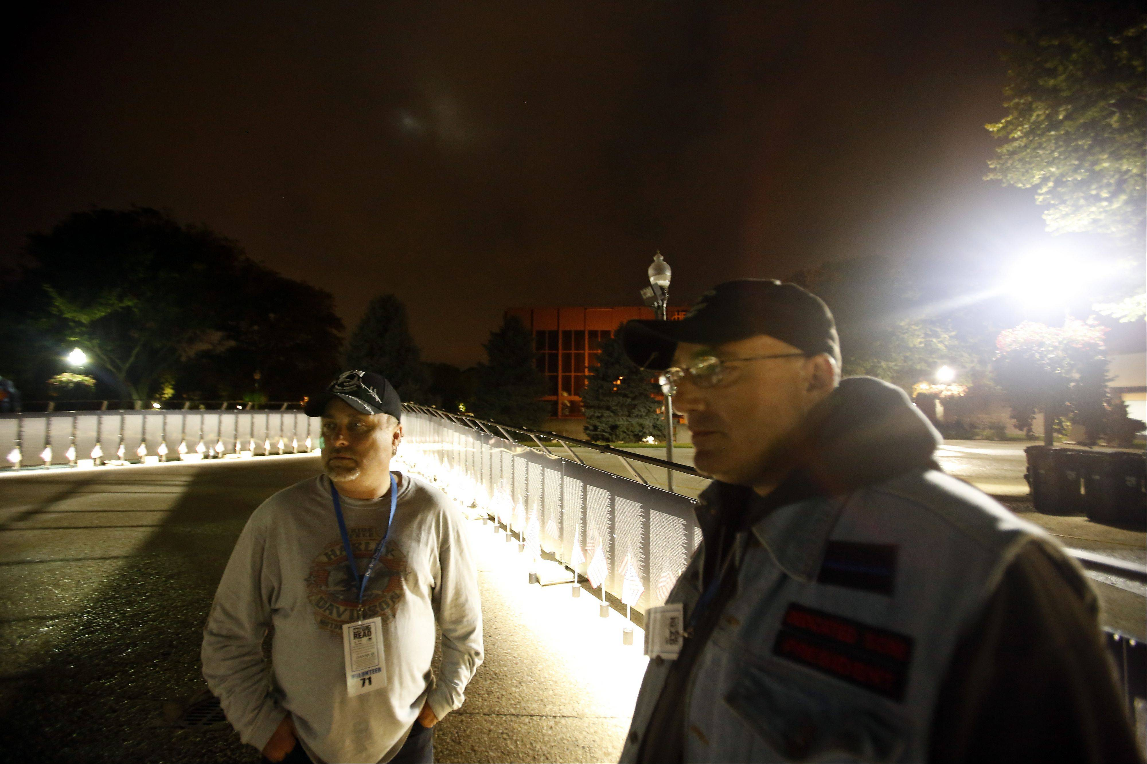 "Volunteers Don Wells of Roselle and Bill Glisson of Batavia reflect on their night spent with ""The Wall That Heals"" in Elgin. Both men planned to return and work overnight Friday."