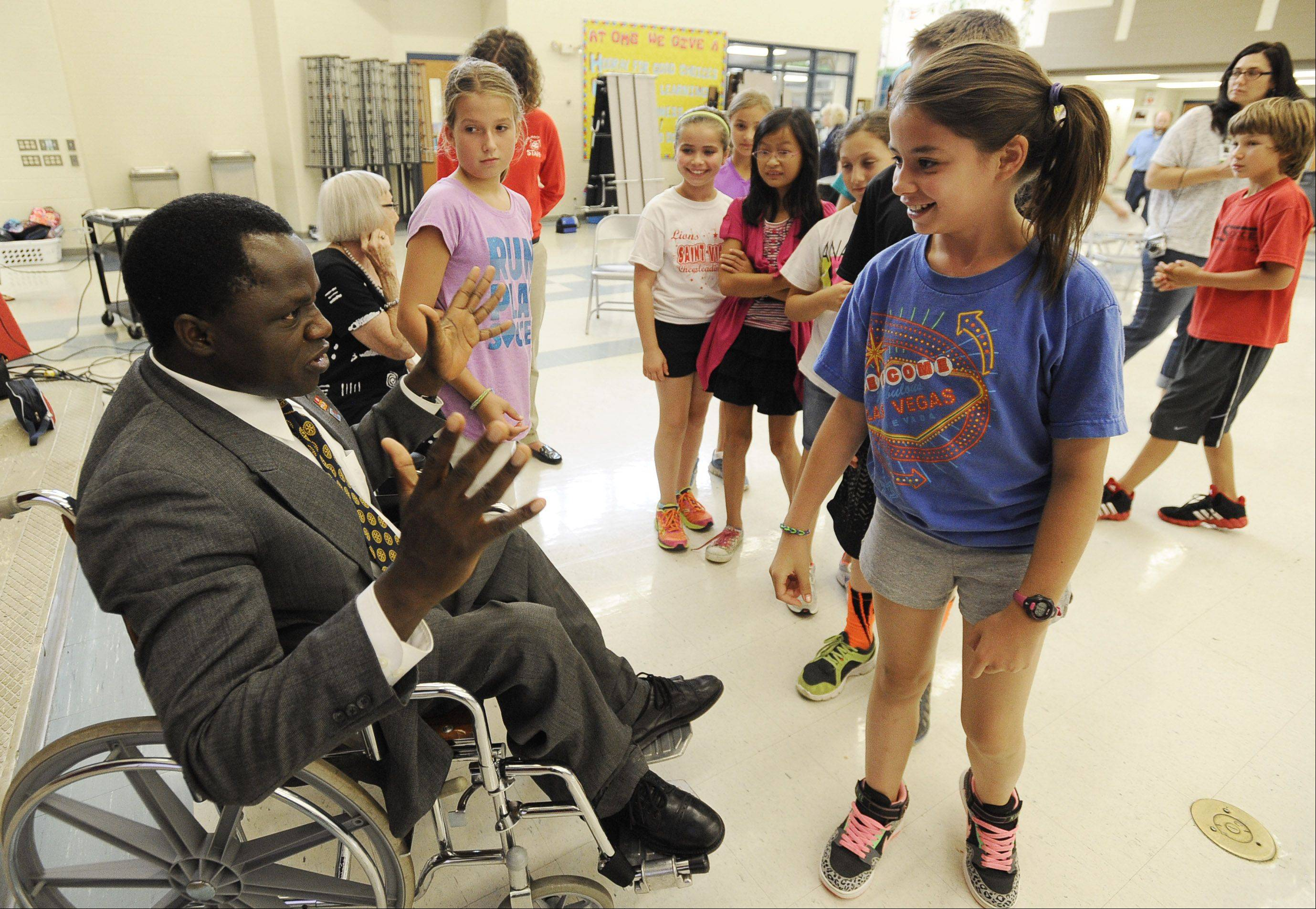 Polio survivor Ayuba Gufwan tells Amanda Hegel, 11, who is in the fifth grade at Olive-Mary Stitt Elementary in Arlington Heights, about how he started Wheelchairs for Nigeria.