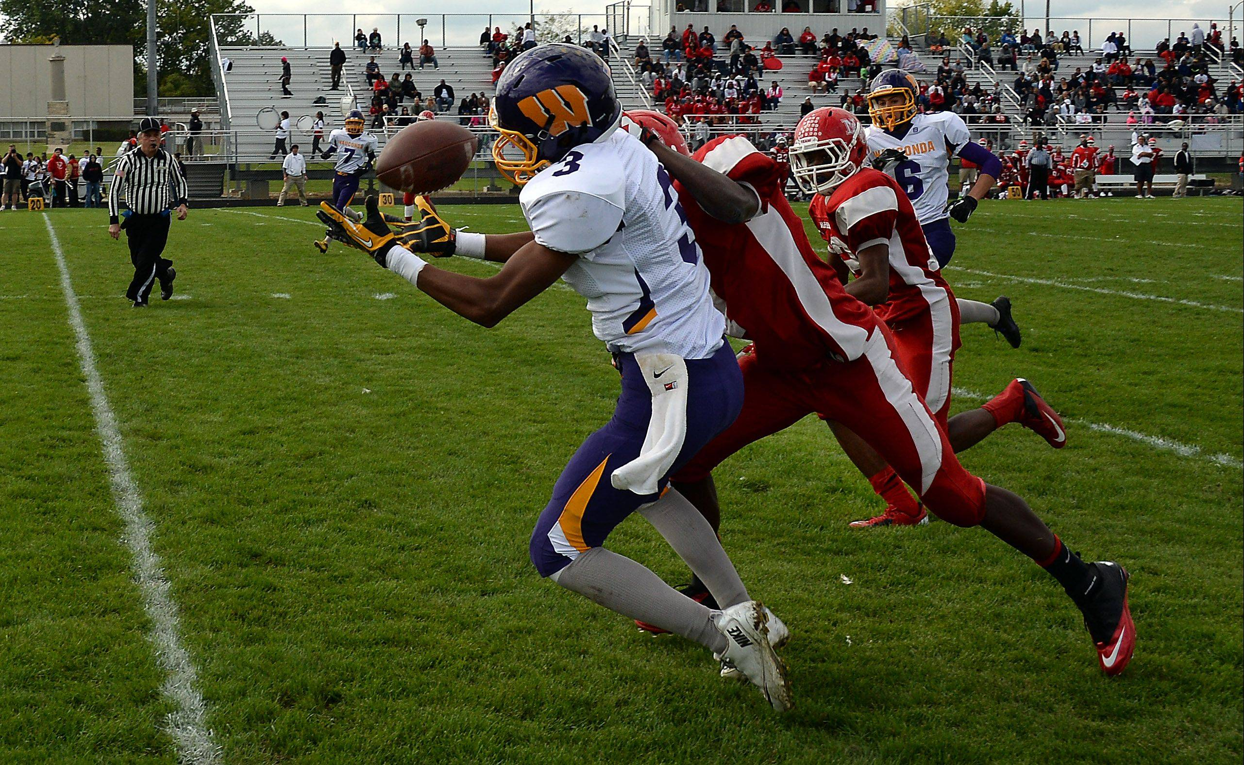 Wauconda�s Josh Anderson hauls in a pass play despite pressure from North Chicago�s Brandon Coofer in the second quarter for major yardage at North Chicago on Saturday.