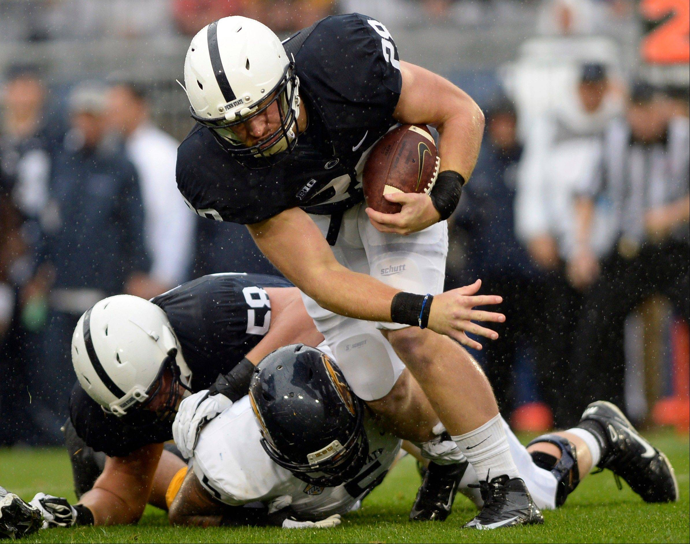 Penn State running back Zach Zwinak tries to elude Kent State defensive lineman Roosevelt Nix in the first half of Saturday�s game in State College, Pa.