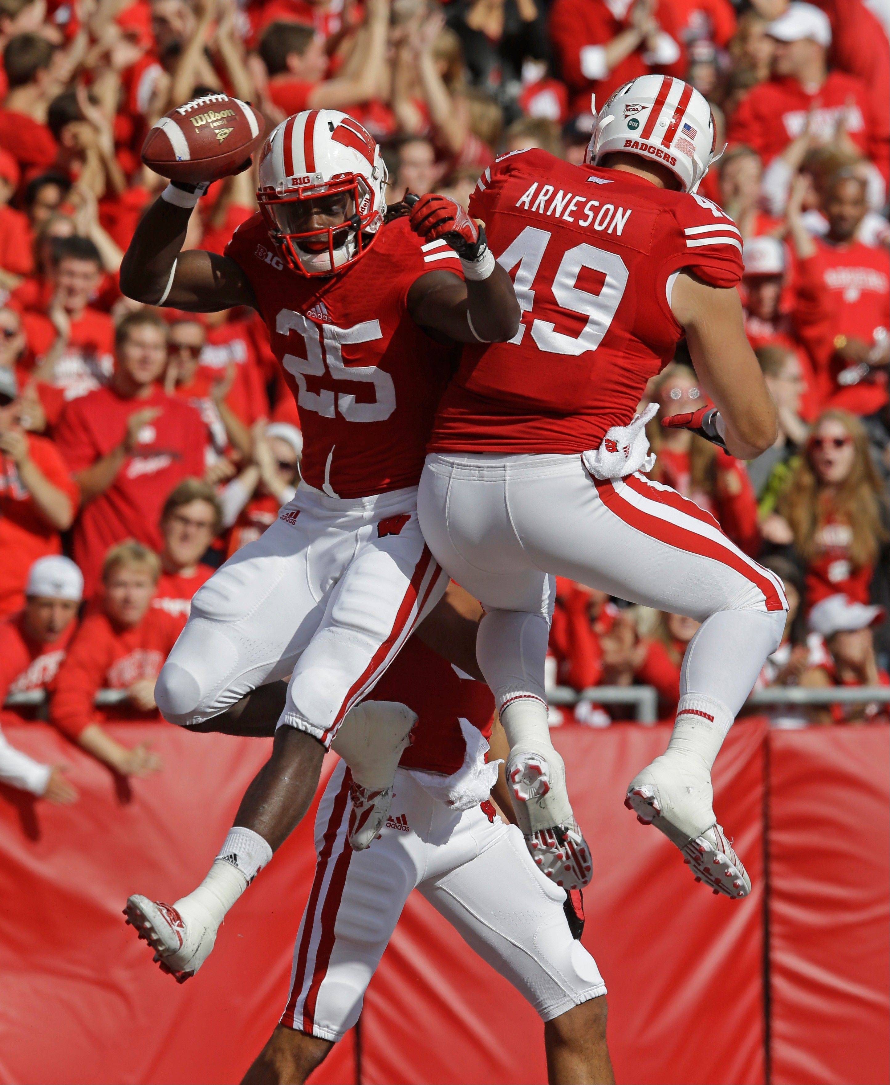 Wisconsin�s Melvin Gordon (25) celebrates his touchdown run with teammate Sam Arneson (49) during the first half of Saturday�s game against Purdue in Madison.