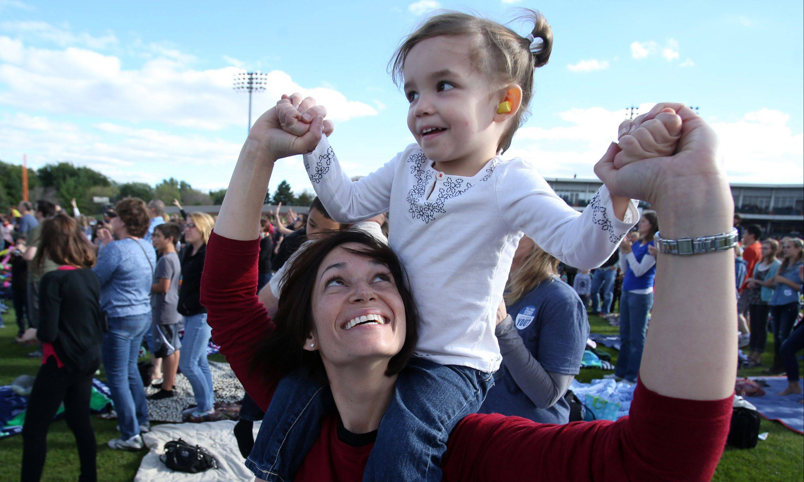 Three-year-old Clara Keith and mom, Rebecca, of Barrington, sway to the music of the Vertical Church Band Saturday at Harvest Bible Chapel's 25th anniversary celebration at Boomers Stadium in Schaumburg.