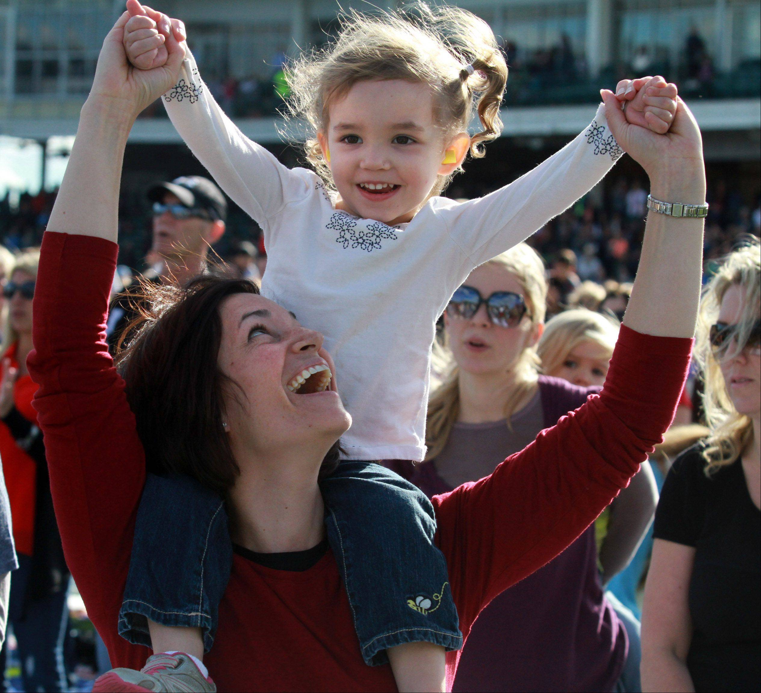 Three-year-old Clara Keith and mom, Rebecca, of Barrington, sway to the music of the Vertical Church Band at Harvest Bible Chapel's 25th anniversary celebration Saturday at Boomers Stadium in Schaumburg.