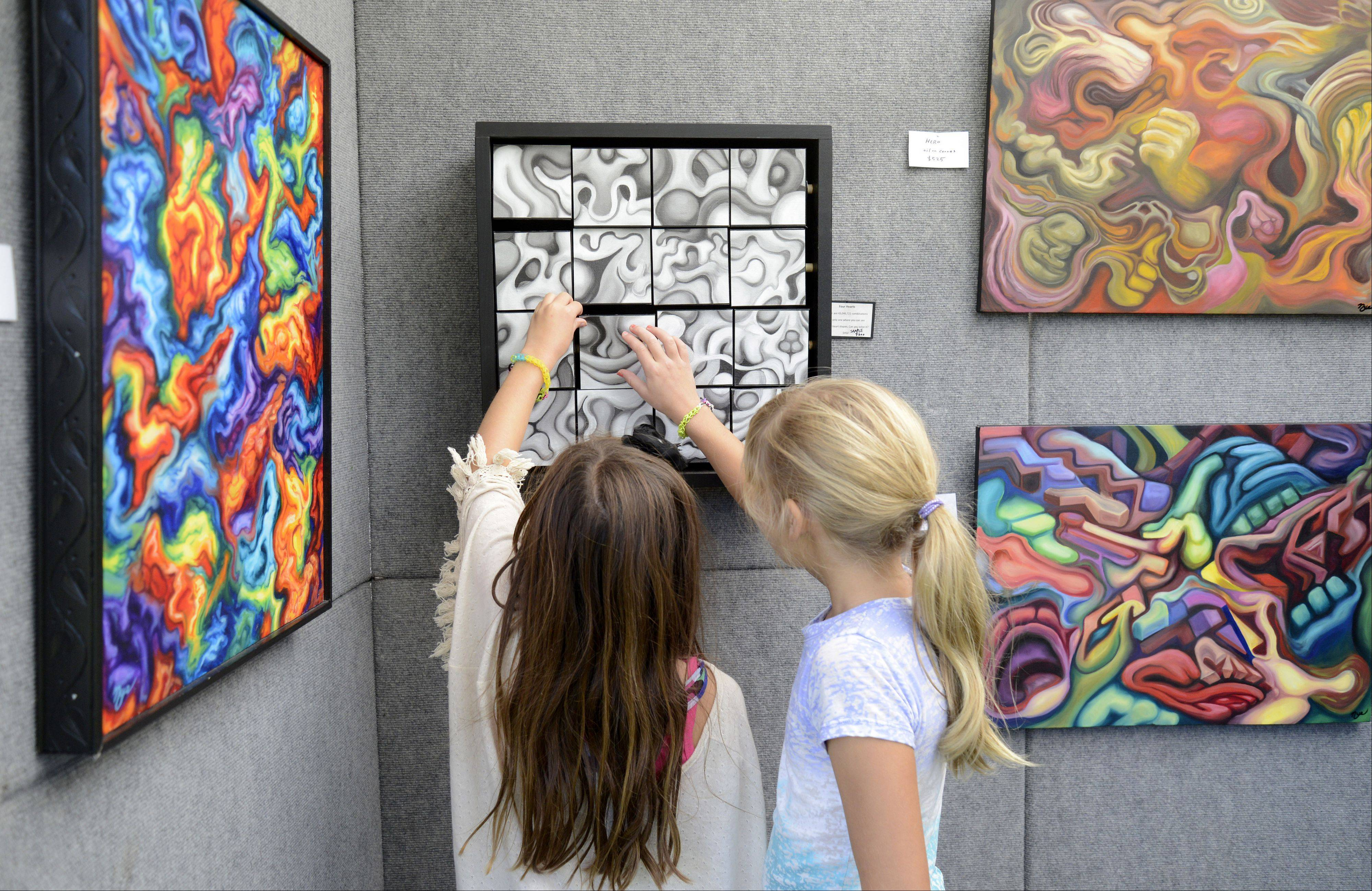 Hanna Christian, left, and Meredith Brown, both 8½and from Batavia, explore the interactive artwork of Eric Nye of Des Plaines at the Art in Your Eye festival Saturday in Batavia. Nye, who has been doing mixed media art for 15 years, uses images, paints and other media to create different scenes.