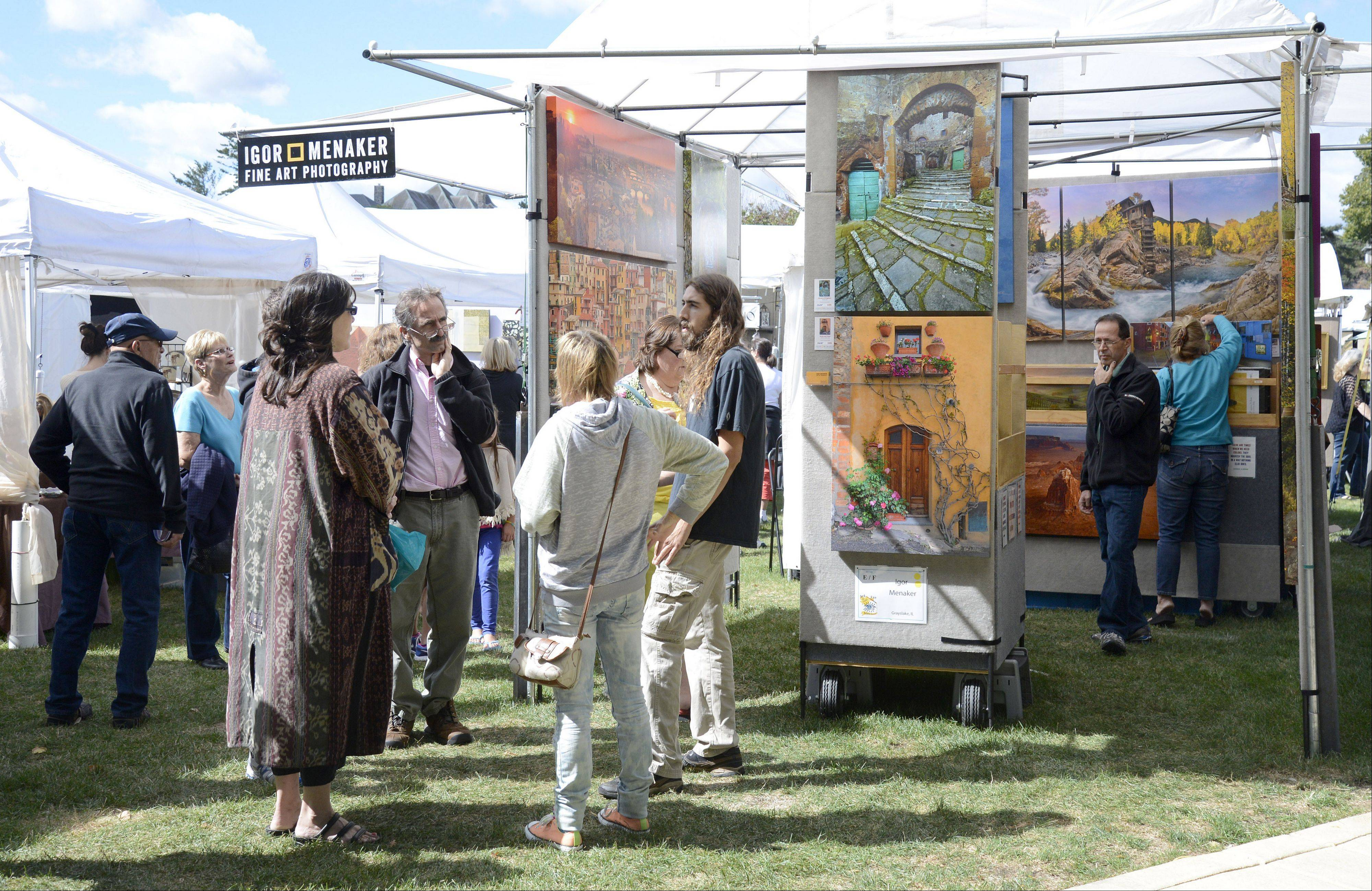 People gather at Igor Menaker's tent at the Art in Your Eye festival Saturday in Batavia. Menaker, a photographer from Grayslake, took part in the festival for first time. He said his favorite places to photograph are Colorado and Italy's Tuscany region.