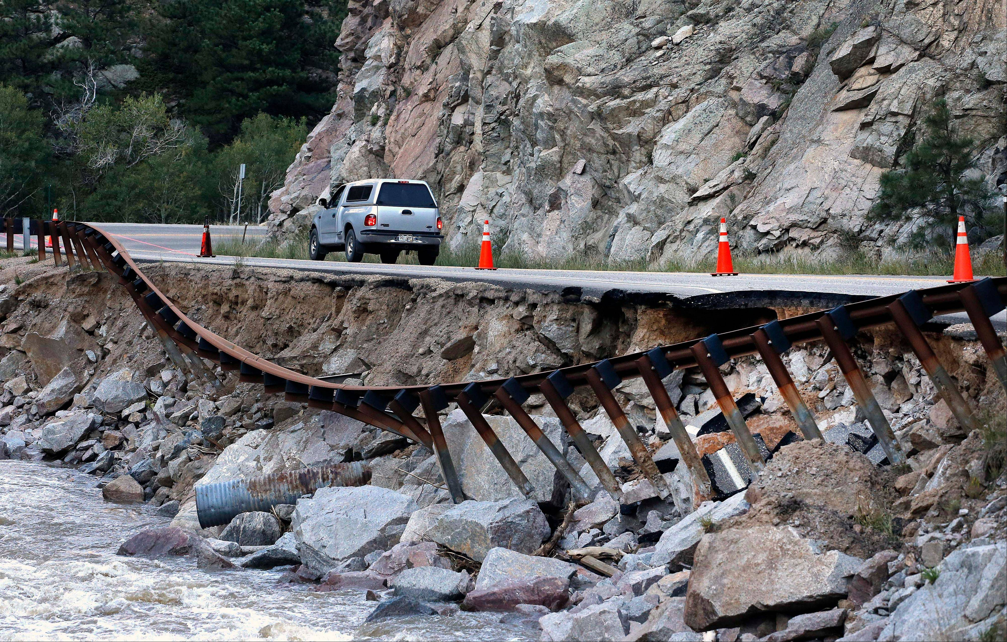 A guardrail hangs away from a closed canyon road Friday, where some local residents are allowed to drive with caution, and which is washed out in places by recent flooding, up Boulder Canyon, west of Boulder, Colo.