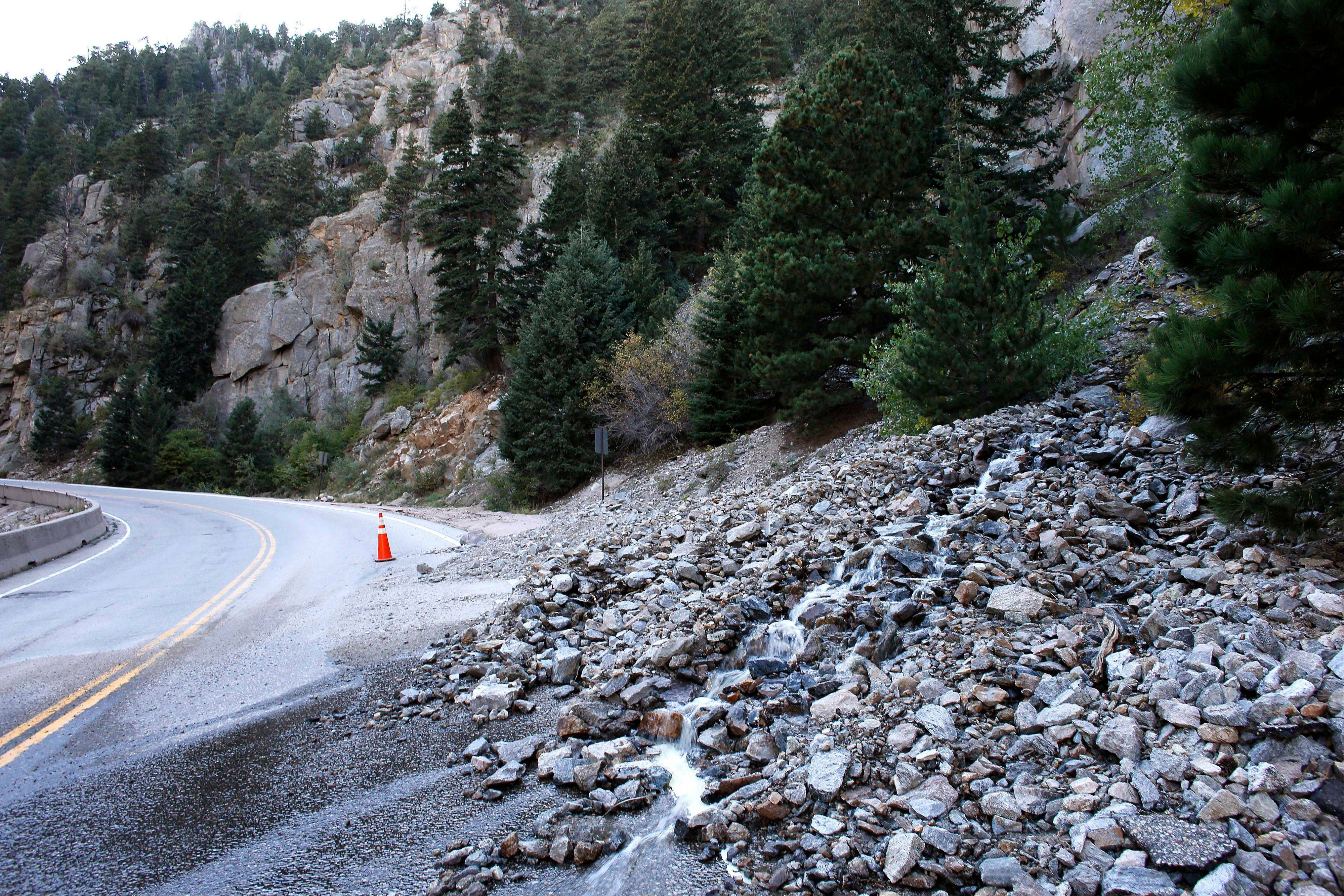 A rock slide partially blocks a closed canyon road, which links Boulder with the mountain town of Nederland.