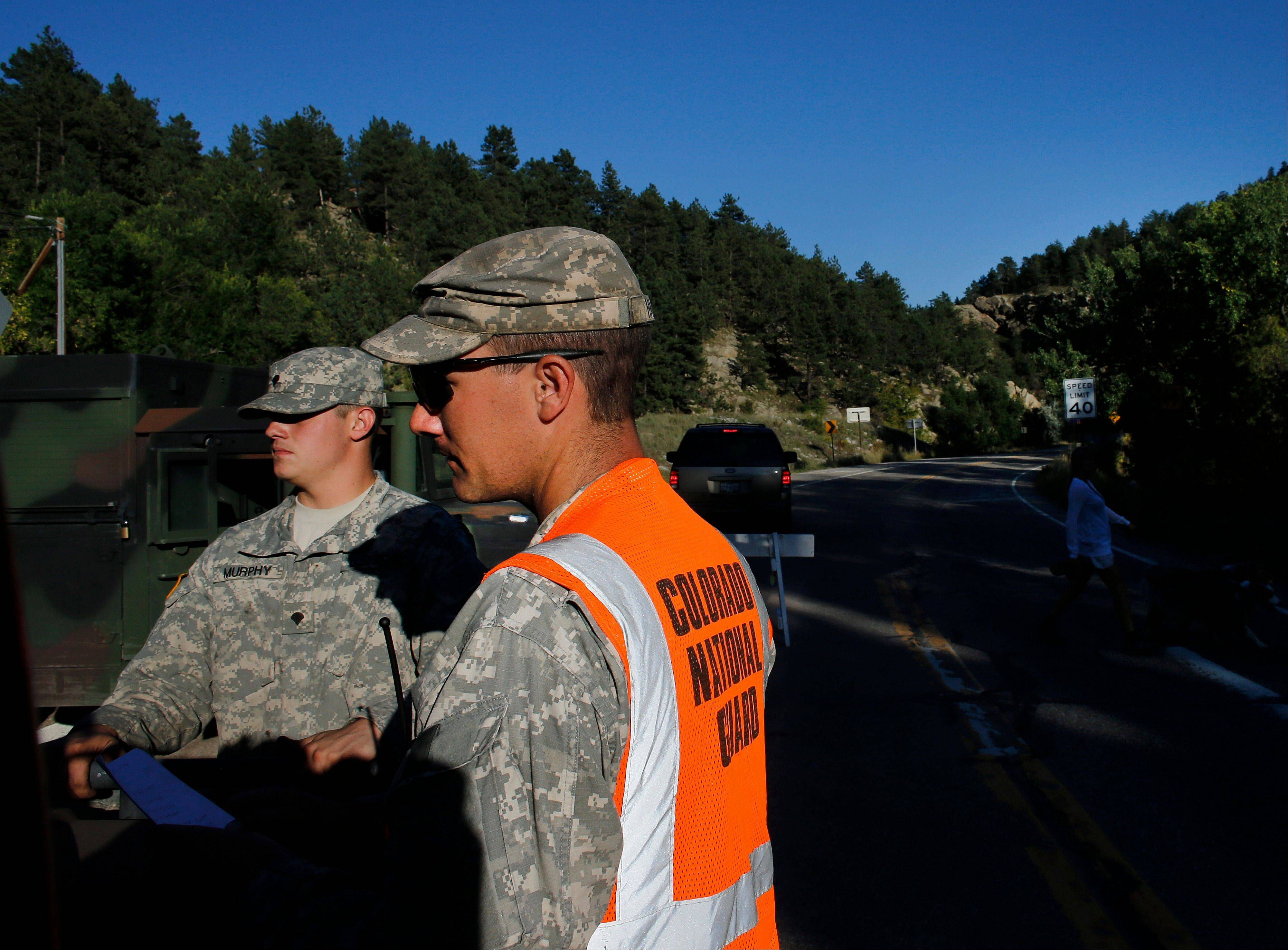 National Guard soldiers man a checkpoint on a closed canyon road, which is washed out in places by recent flooding, west of Boulder, Colo.