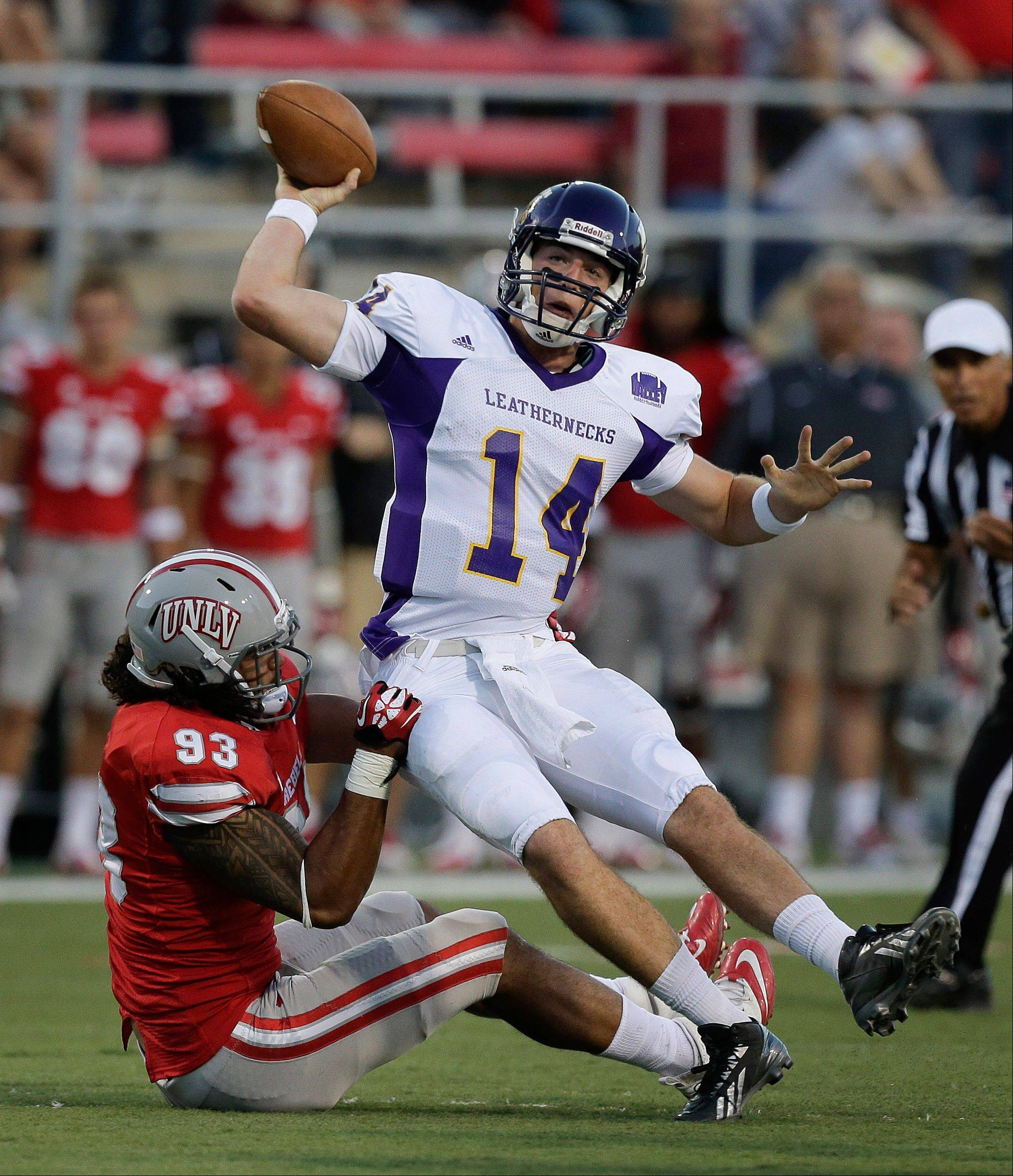 UNLV lineman Sonny Sanitoa sacks Western Illinois quarterback Trenton Norvell in the first quarter of Saturday night's game in Las Vegas.