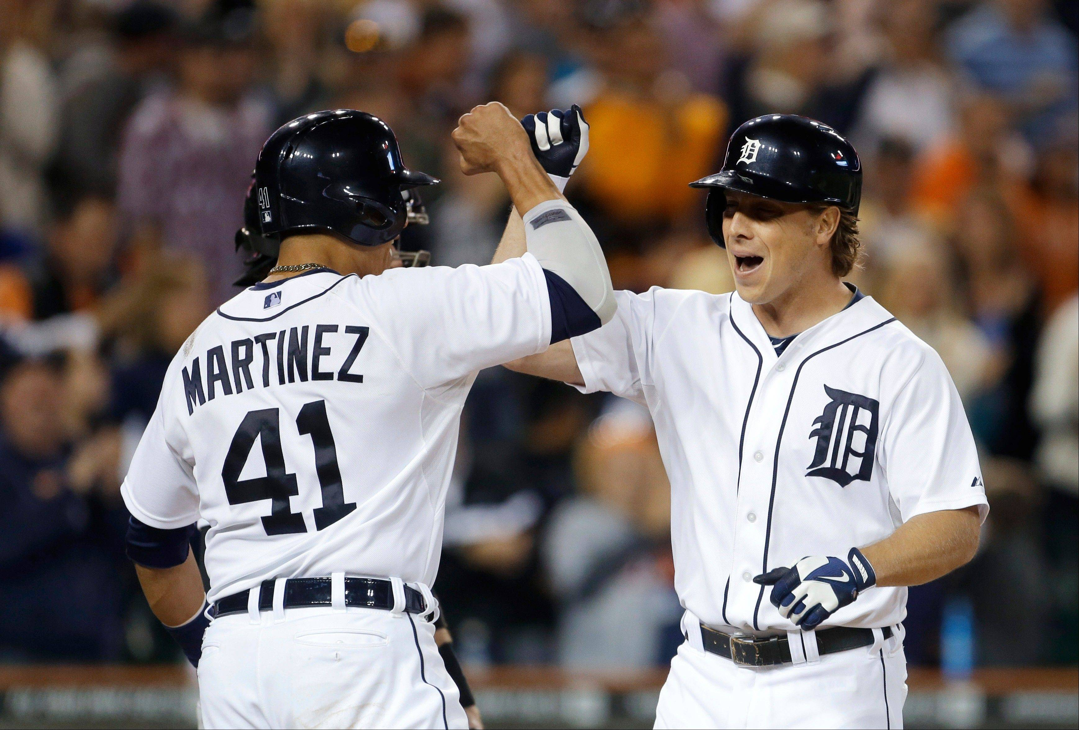 The Tigers' Andy Dirks, right, is congratulated for his three-run home run by Victor Martinez during the ninth inning Saturday night against the White Sox in Detroit.