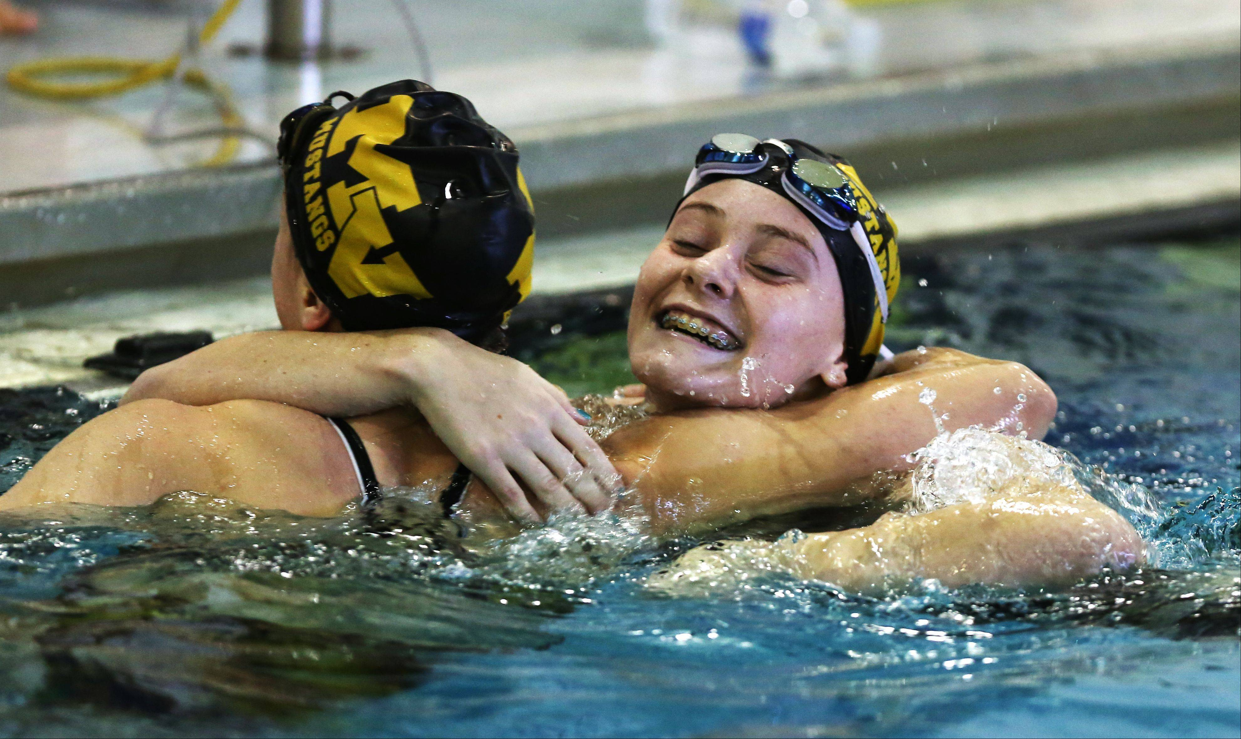 Metea Valley's Amanda Burson, right, hugs teammate Madie Sandberg, left, after winning the 50-yard freestyle, during the girls swimming's Wildcat Invite at West Chicago High School.