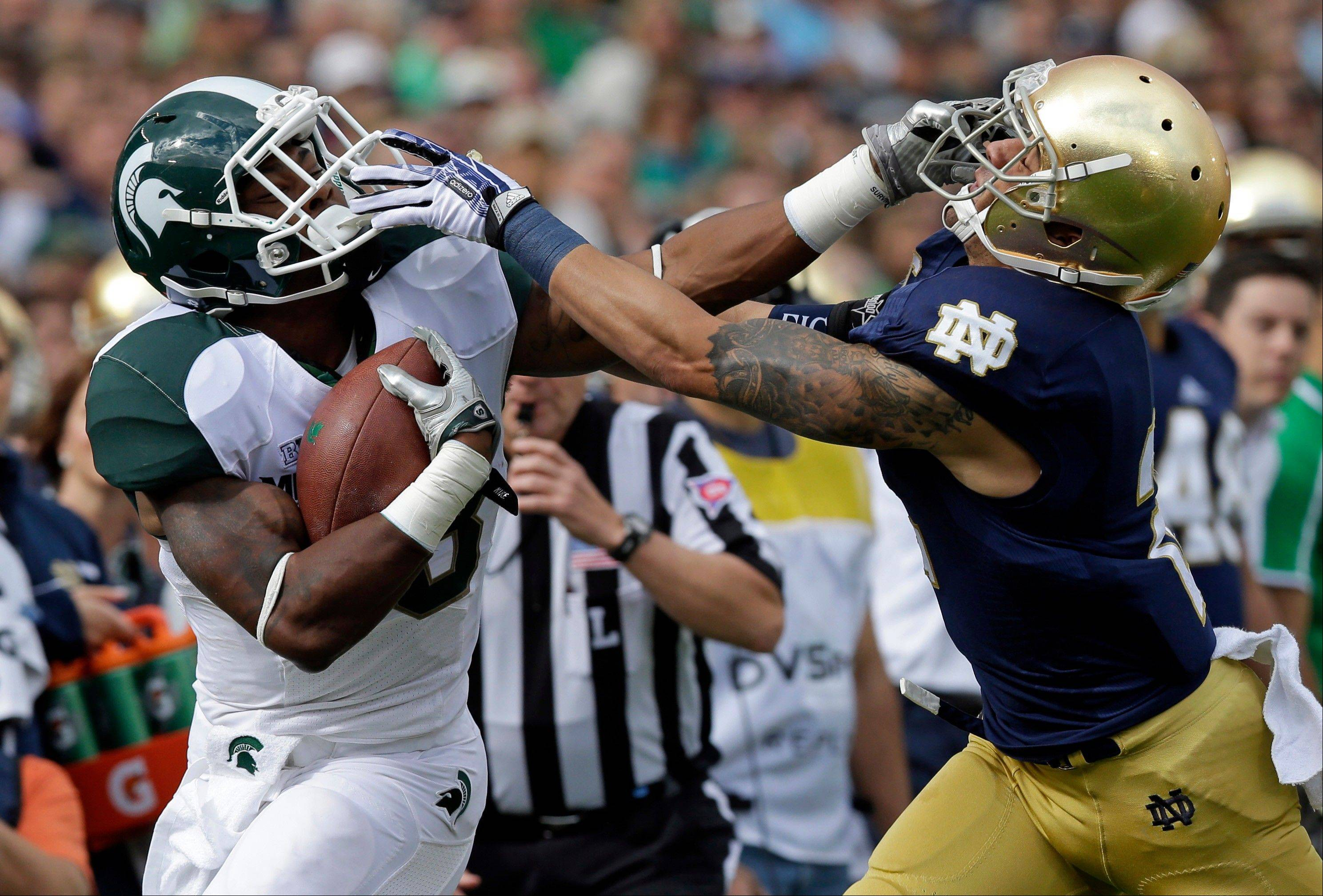 Michigan State running back Jeremy Langford, left, battles with Notre Dame cornerback Bennett Jackson to pick up yardage during the first half Saturday's in South Bend, Ind.