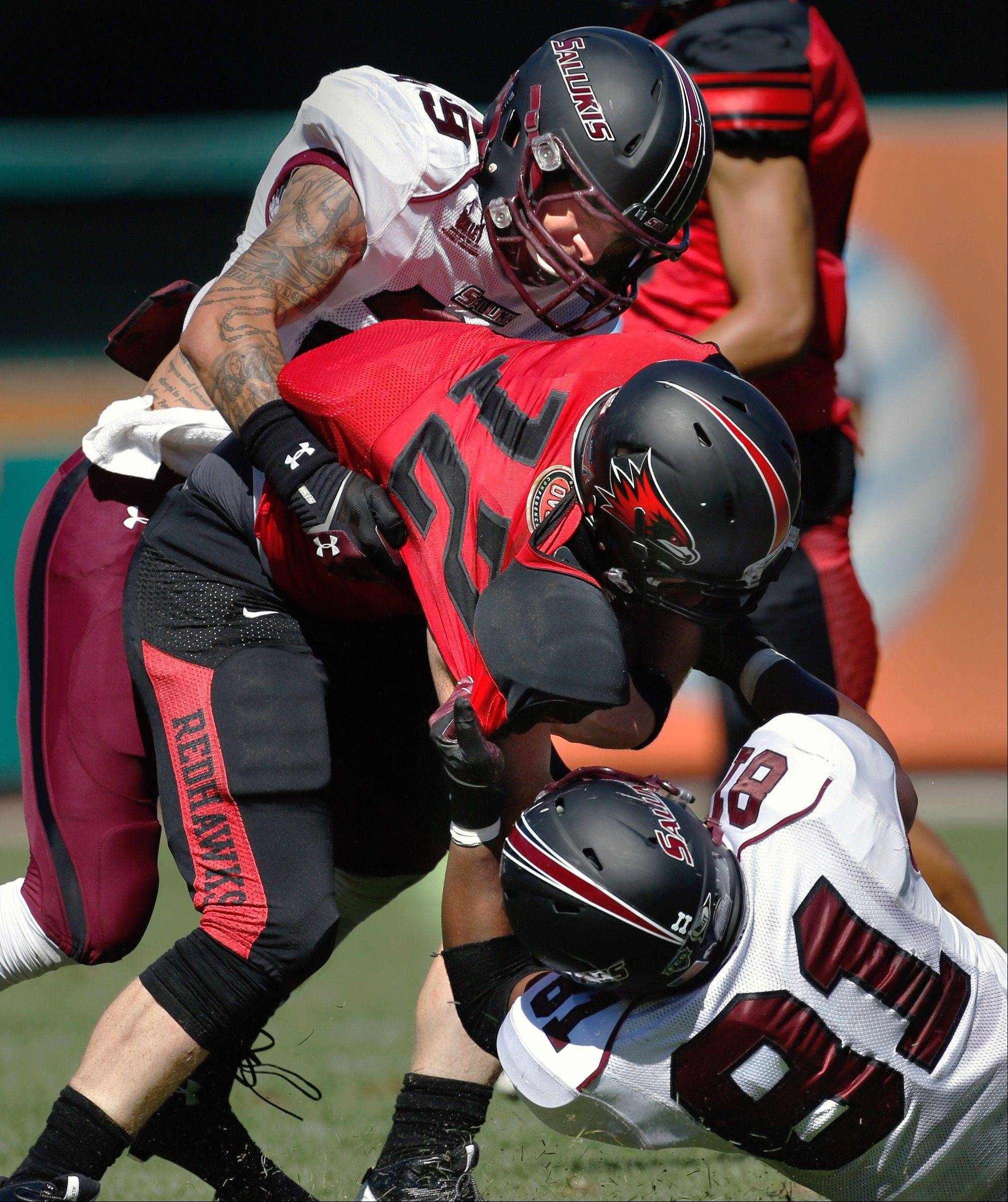 Southern Illinois defenders Boo Rodgers, top, and Leonard Garron bring down Southeast Missouri quarterback Kyle Snyder (12) during the second quarter of Saturday's game at Busch Stadium in St. Louis. SIU won 36-19.