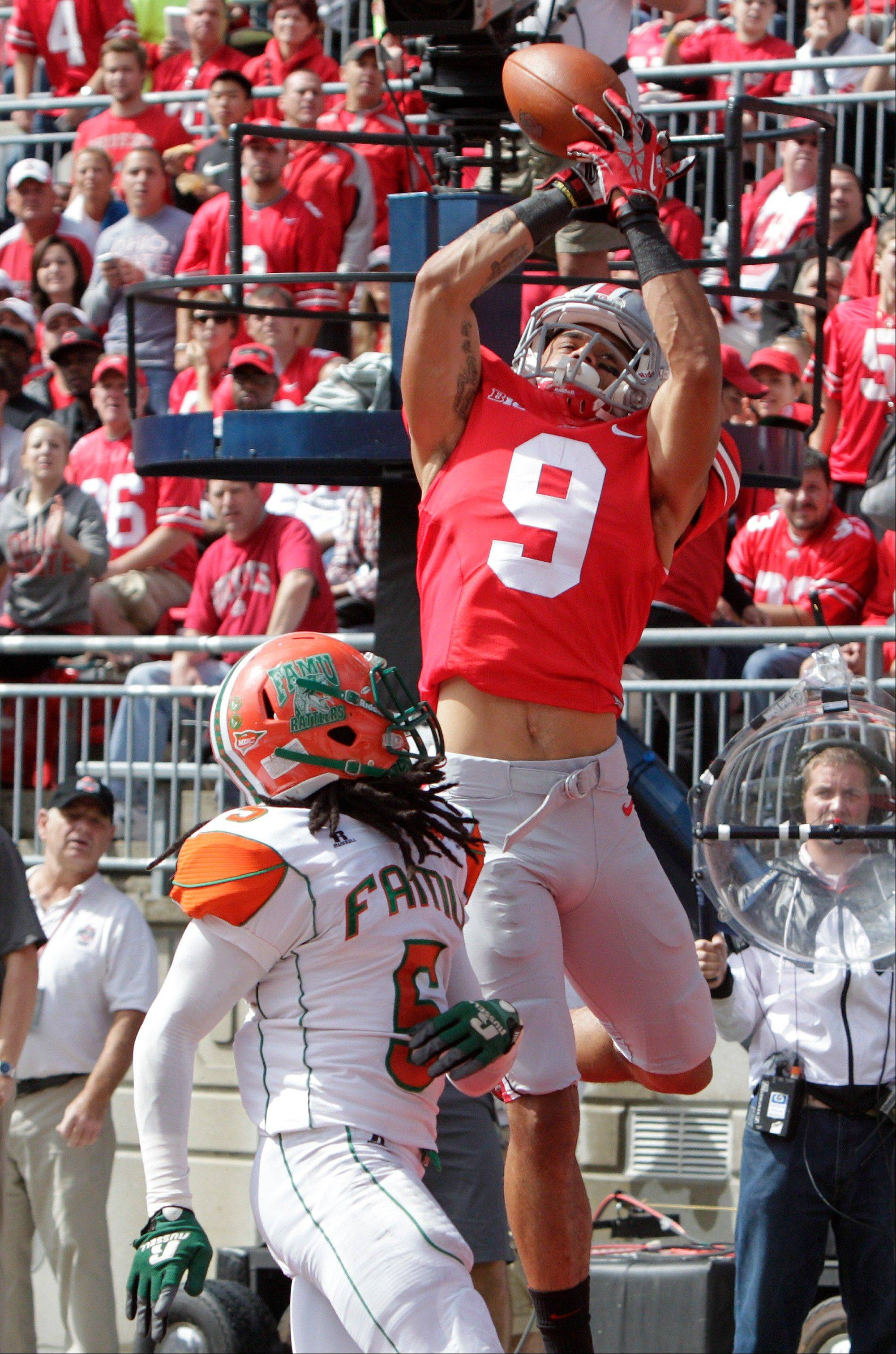 Ohio State wide receiver Devin Smith, top, catches a touchdown pass over Florida A&M cornerback Patrick Aiken during the first quarter of an NCAA college football game Saturday, Sept. 21, 2013, in Columbus, Ohio.