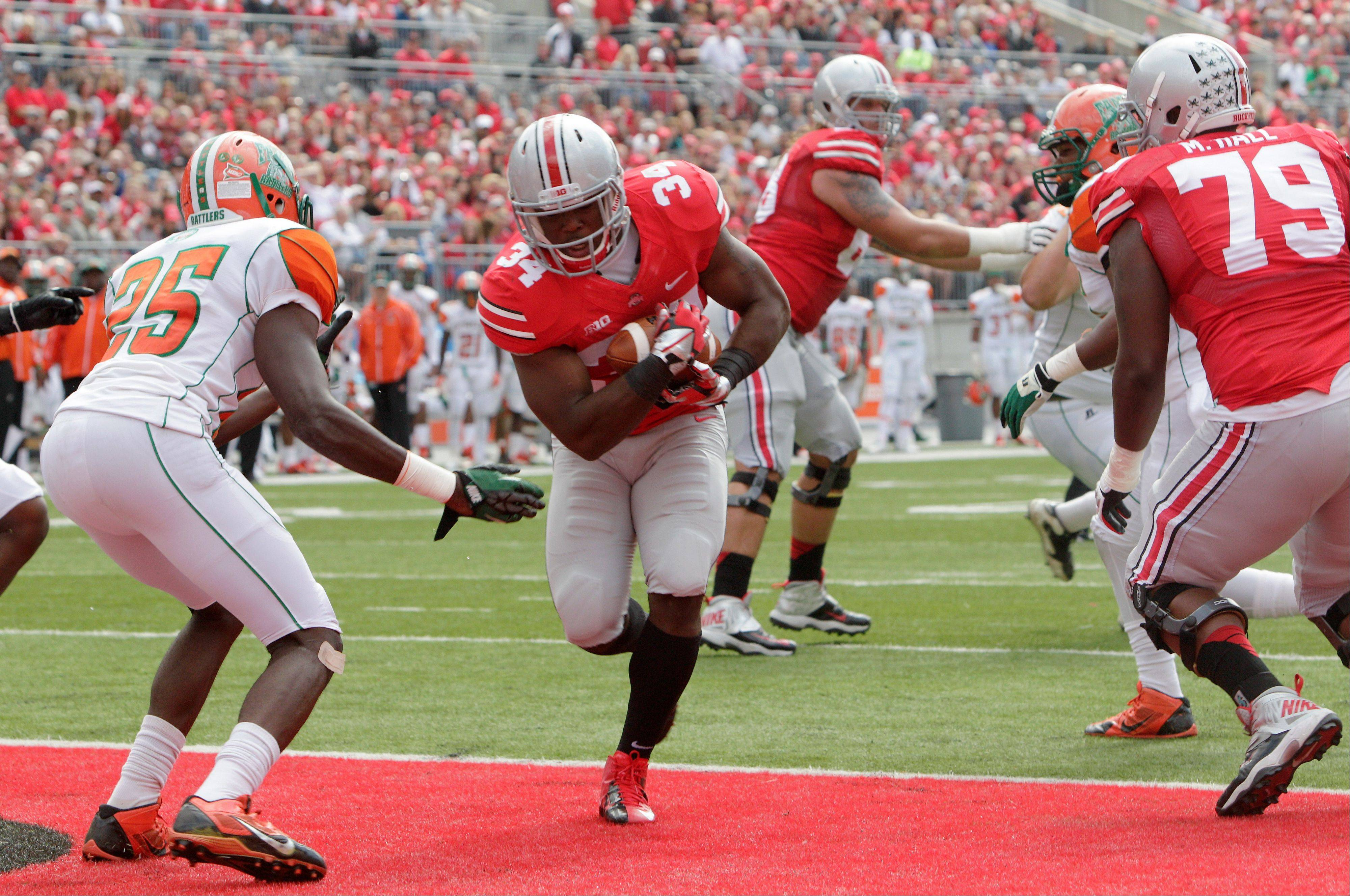 Ohio State running back Carlos Hyde, center, scores a touchdown in front of Florida A&M safety John Oye Ojo (25) during the first quarter of an NCAA college football game Saturday, Sept. 21, 2013, in Columbus, Ohio.