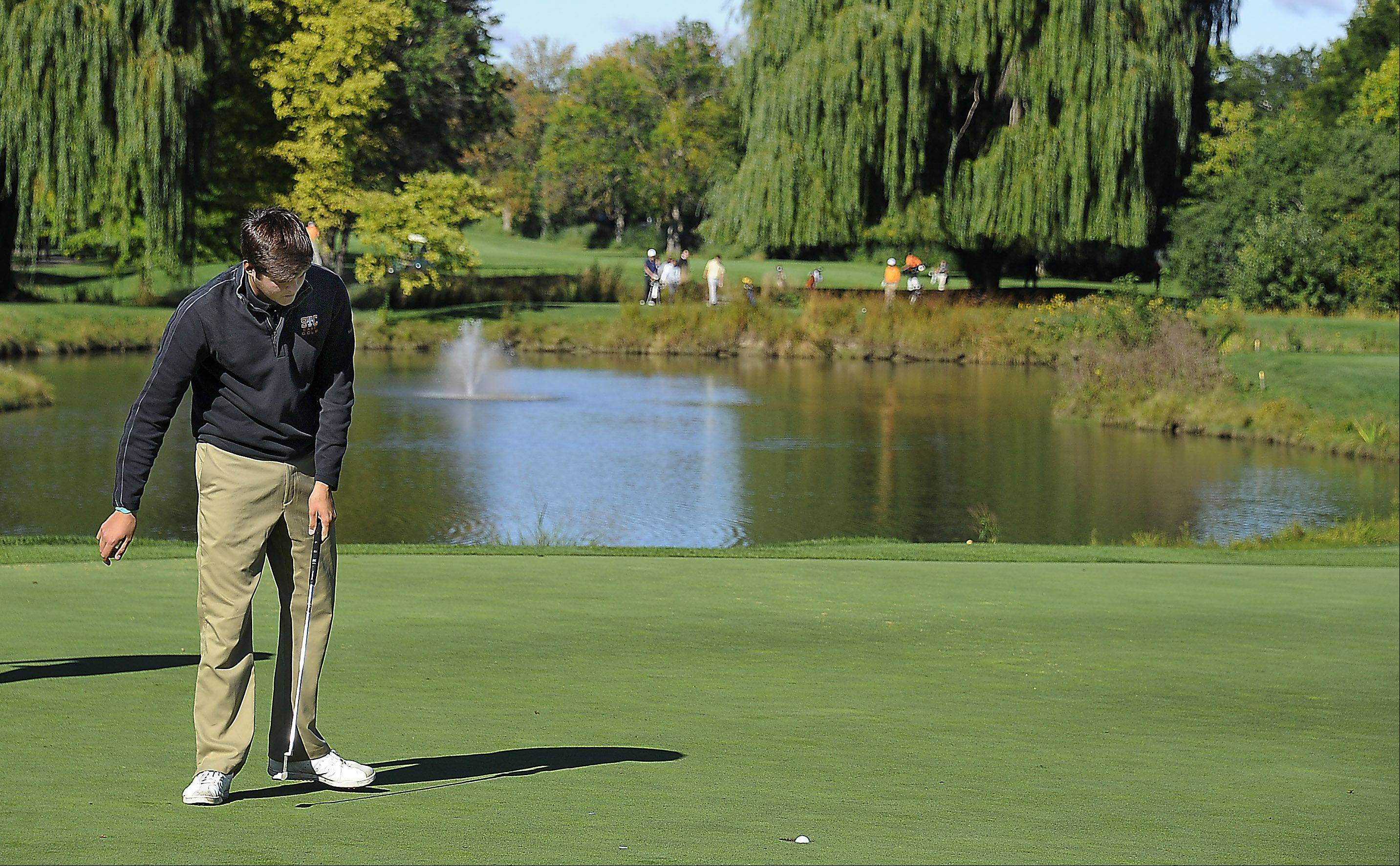 St. Charles East's Kyle Jacobs follows his successful putt at No. 9 at Wheeling's Invitational held at Chevy Chase Golf Club in Wheeling on Saturday.