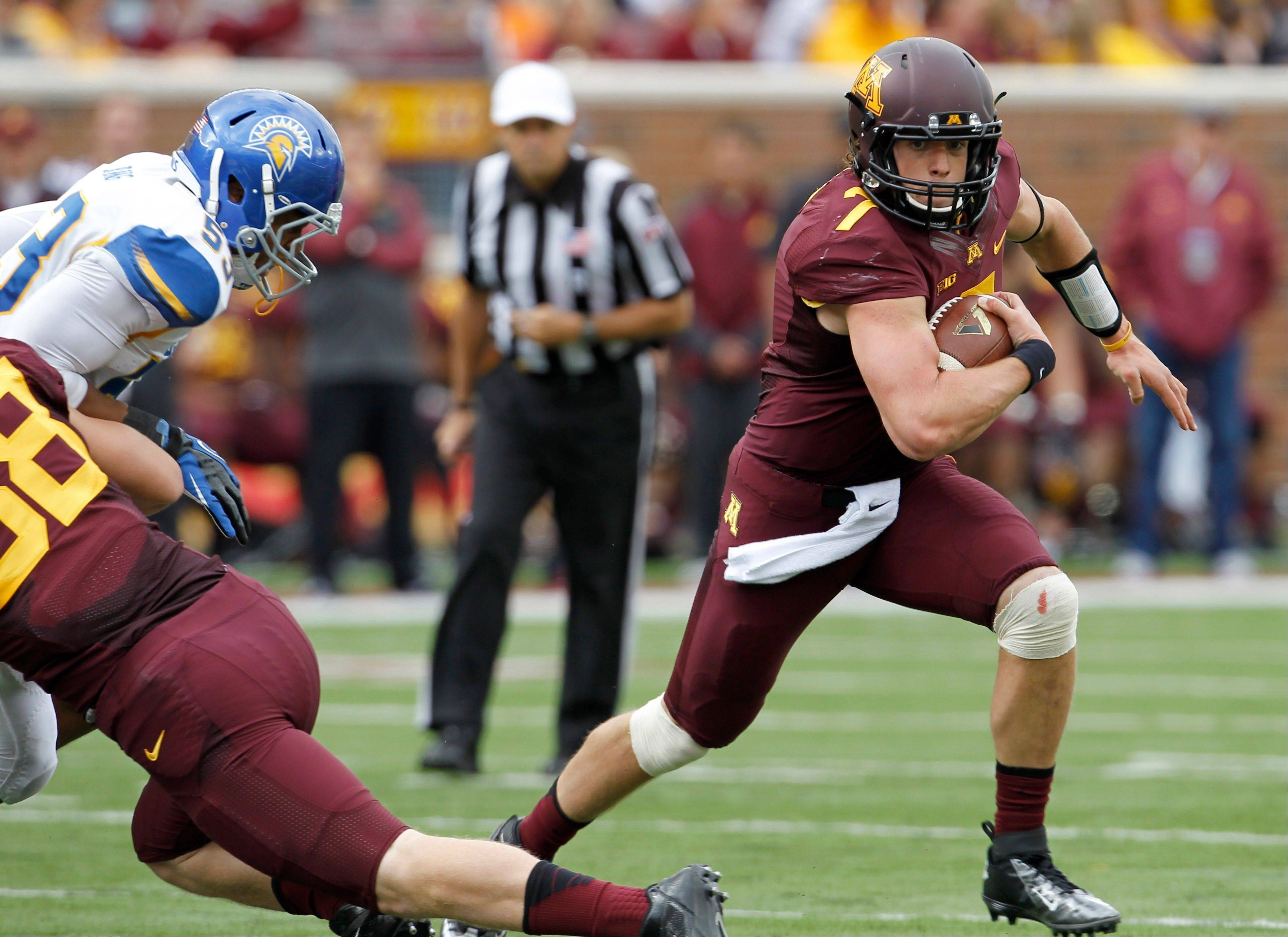Minnesota quarterback Mitch Leidner, right, carries the ball for a 15-yard gain during the first quarter of an NCAA college football game against San Jose State in Minneapolis Saturday, Sept. 21, 2013.