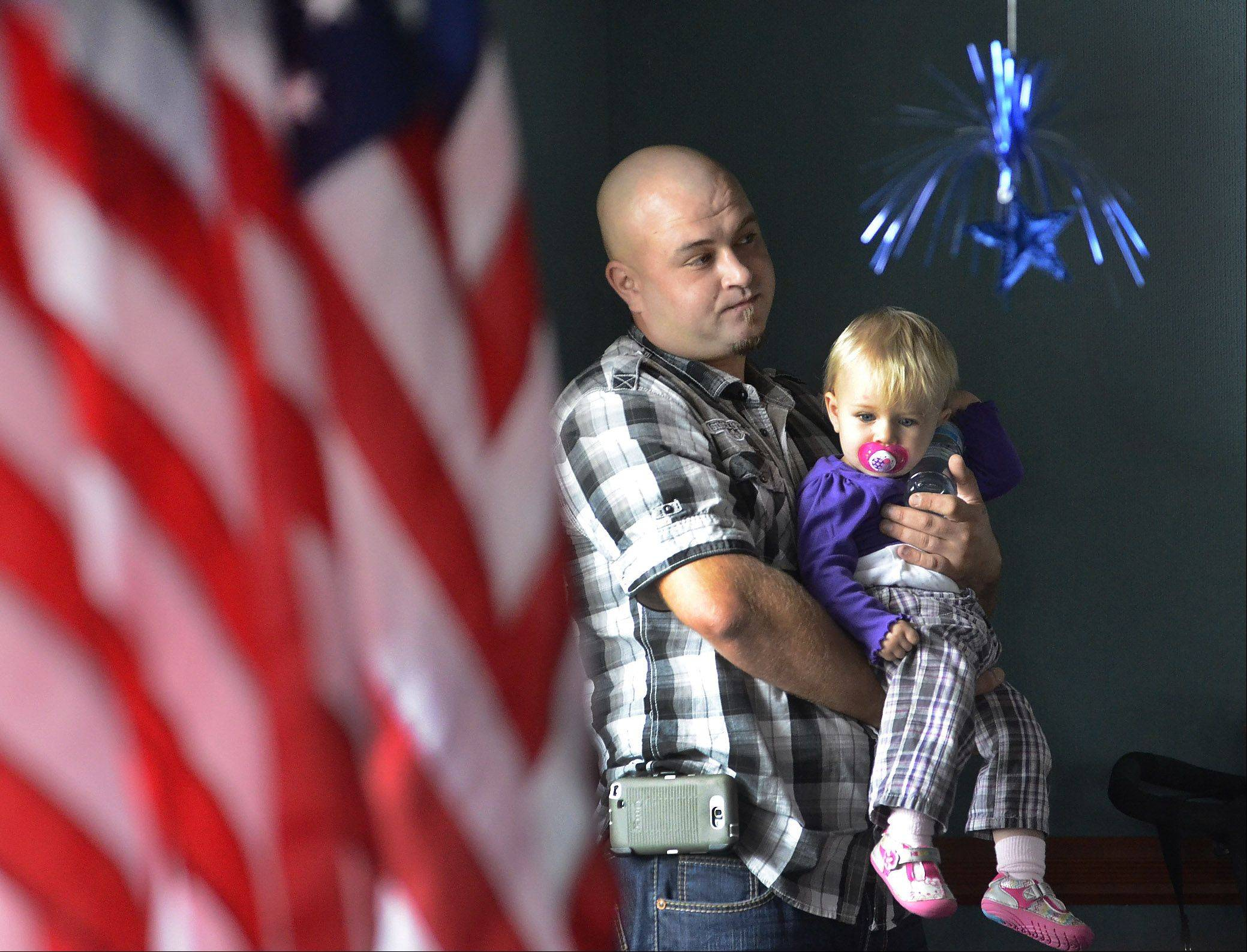 Pawel Gogola, of Algonquin, holds his daughter Natalie while watching his wife Wioletta, of Poland, receive her citizenship during a special naturalization ceremony at the Schaumburg Township District Library, when over 70 individuals received their citizenship.