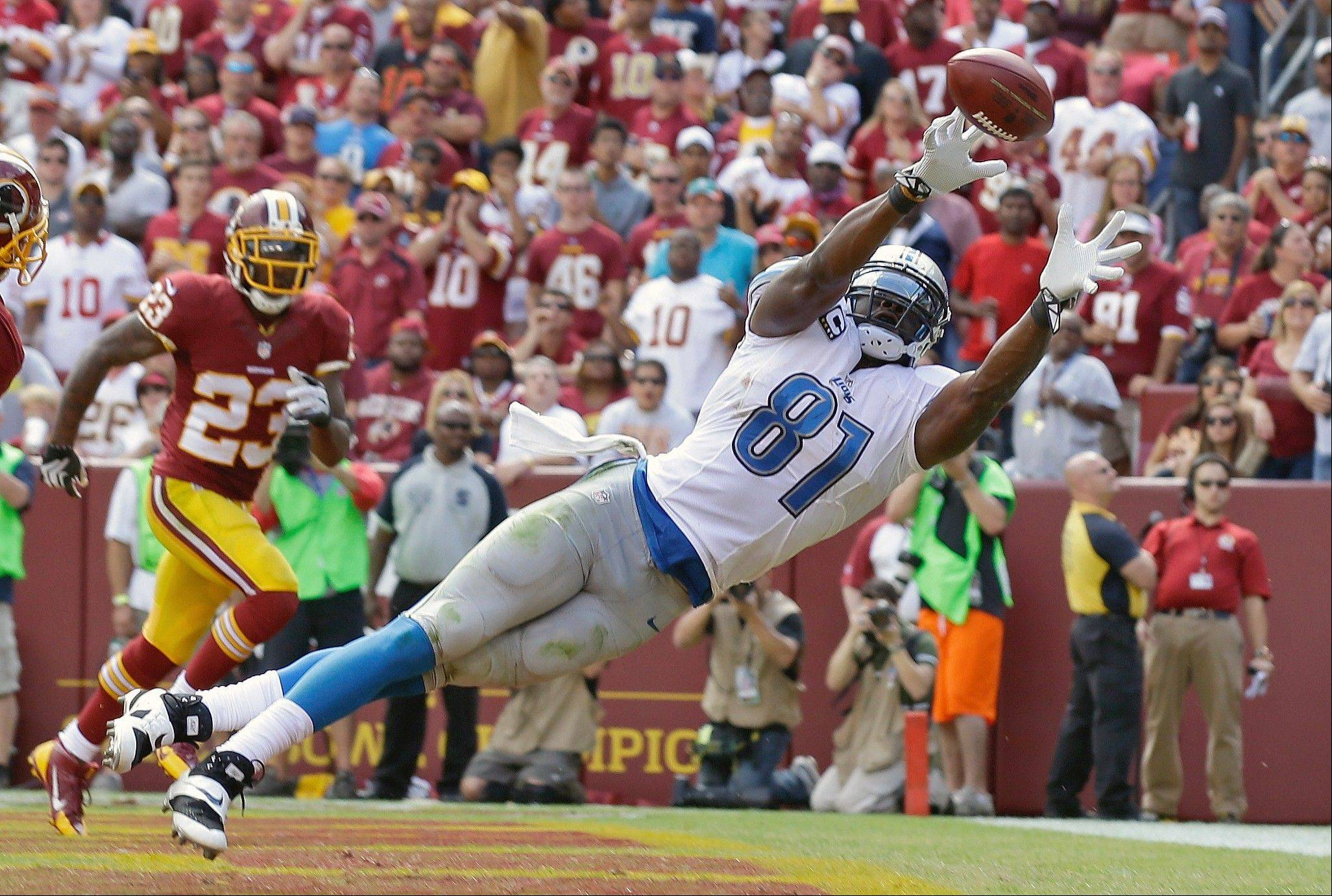 Detroit Lions tight end Brandon Pettigrew can't quite reach a Matthew Stafford pass in the end zone as Washington Redskins cornerback DeAngelo Hall watches in the background during the first half of a NFL football game in Landover, Md., Sunday, Sept. 22, 2013.
