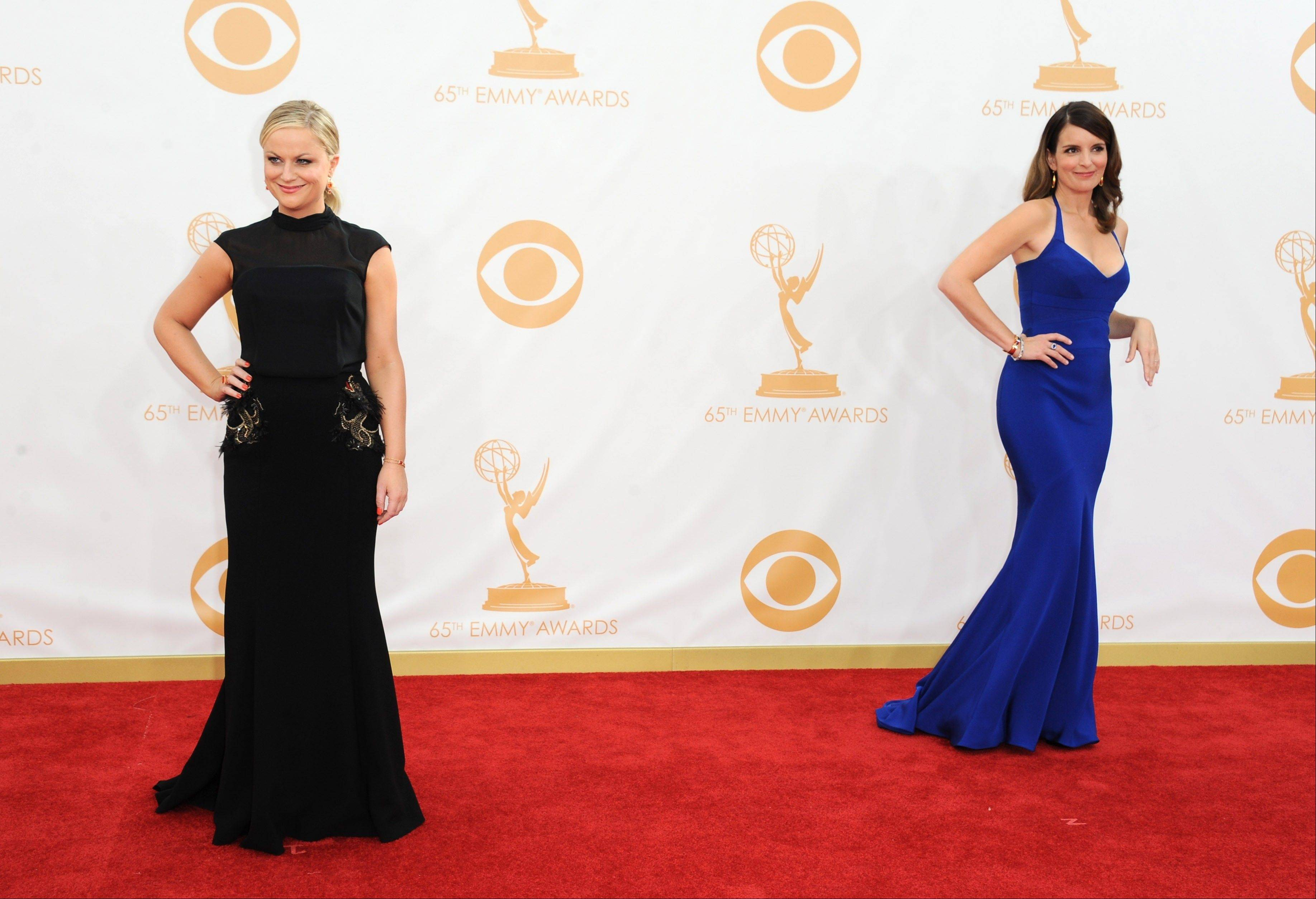 Amy Poehler, wearing Brian Rennie for Basler, left, and Tina Fey, wearing Narciso Rodriguez, arrive at the 65th Primetime Emmy Awards at Nokia Theatre on Sunday in Los Angeles.