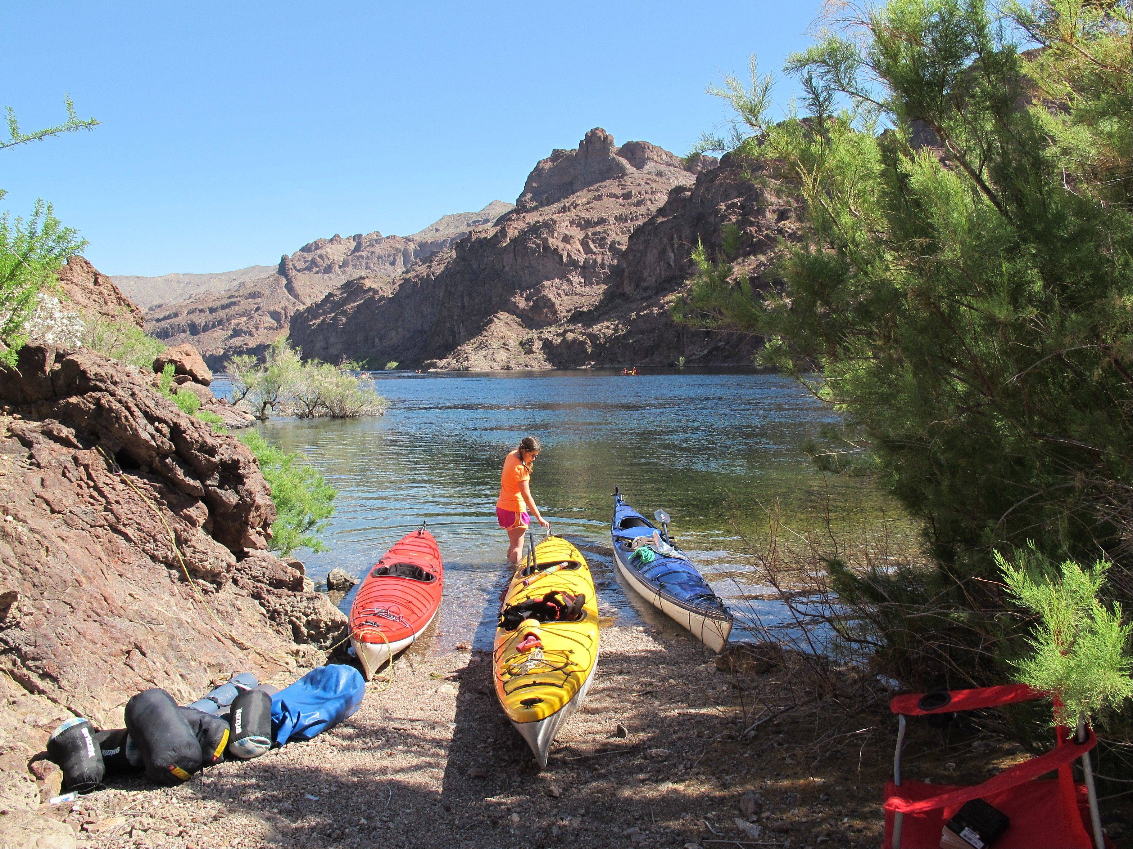 A kayaker with boats on the shore of the Colorado River in Nevada. Outfitters can pick you up at a hotel in Las Vegas first thing in the morning and have you paddling the river through the Black Canyon some 30 miles from Las Vegas before lunch.