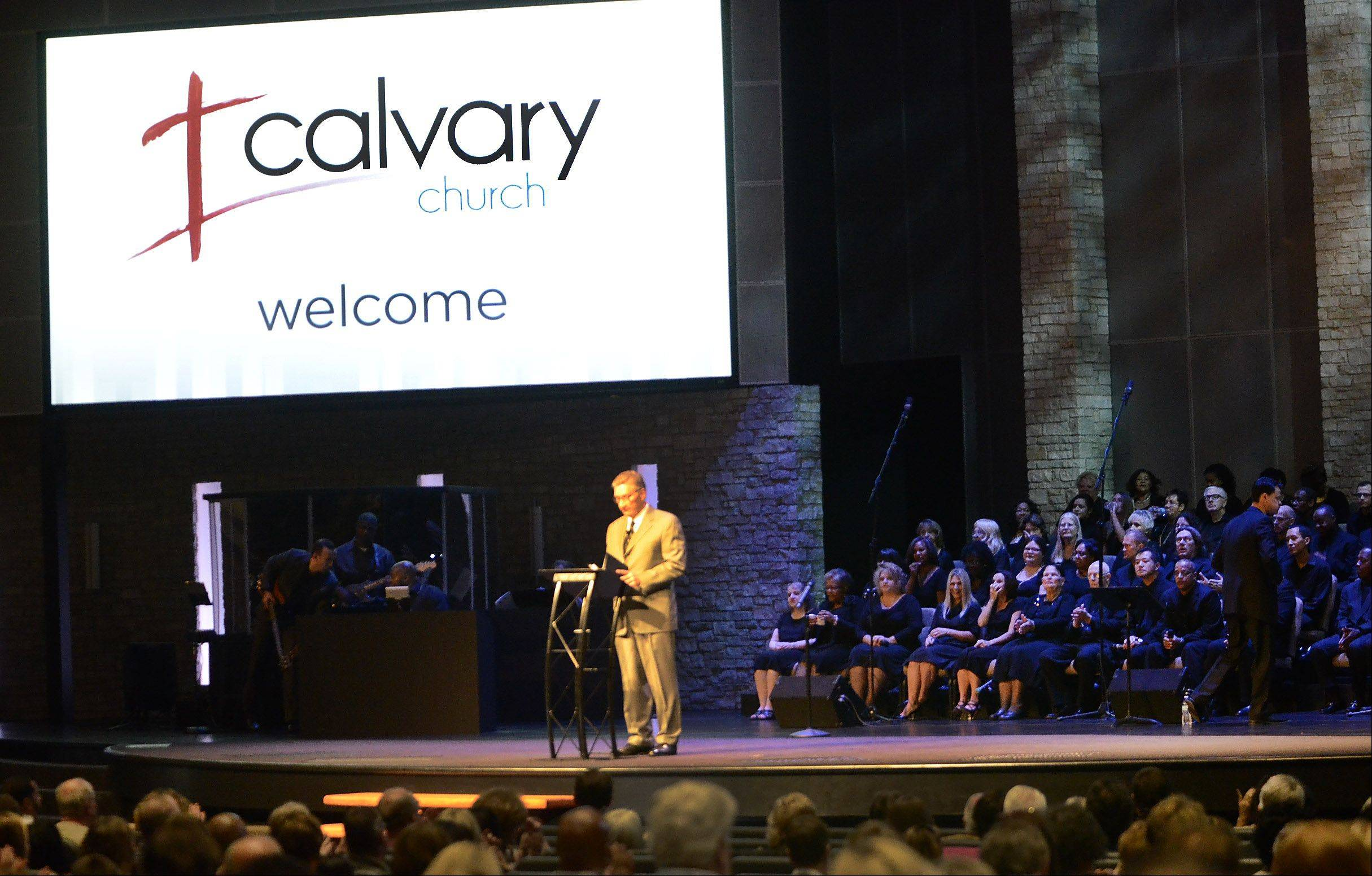 Senior Pastor Randal Ross welcomes the congregation Sunday as Calvary Church in Naperville opened its newly renovated auditorium after more than five months of construction. The choir and orchestra lead the congregation through a history of worship.