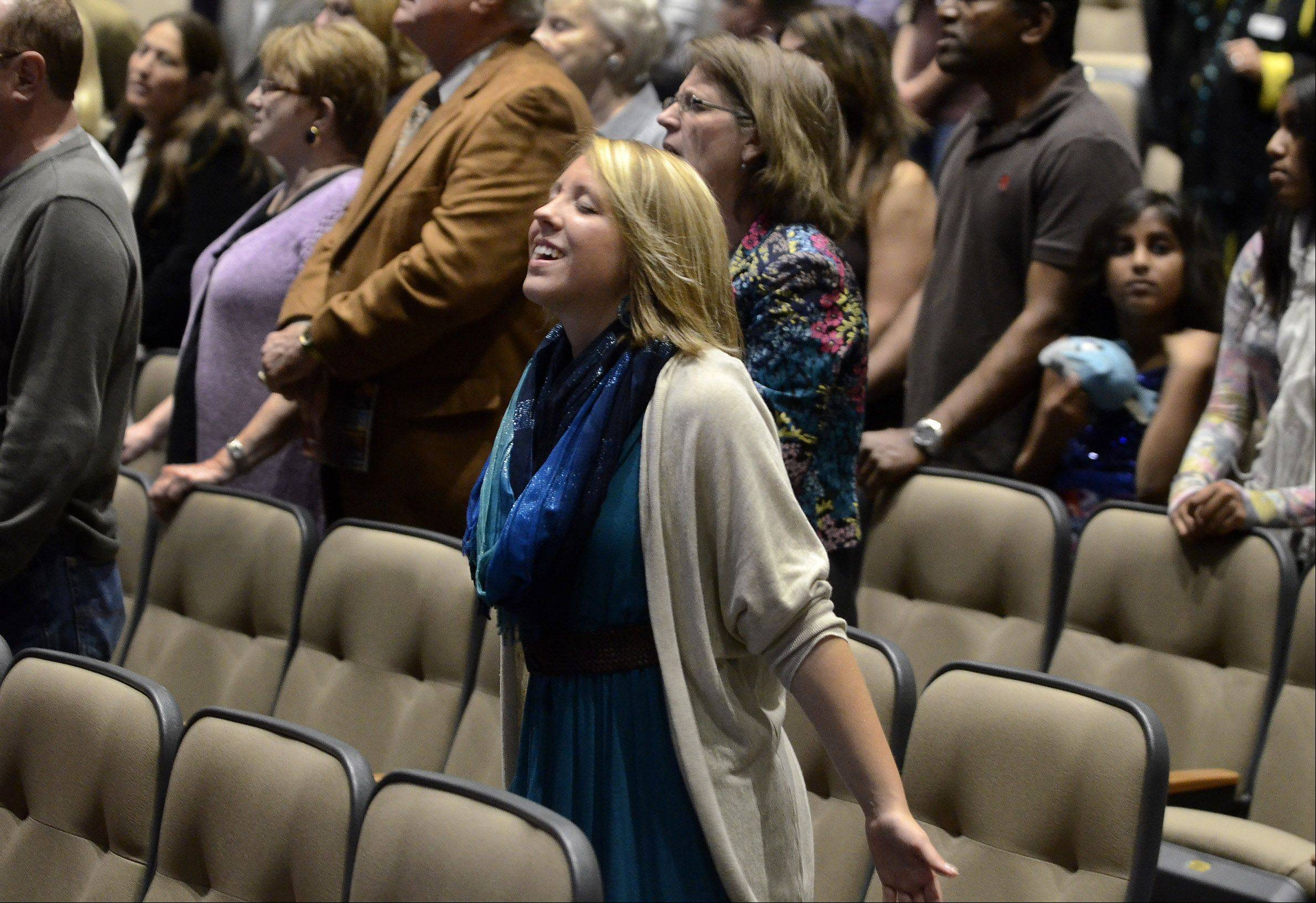 Kelli Schick, of Plainfield, gets absorbed in song as Calvary Church in Naperville opened its newly renovated auditorium Sunday after more than five months of construction. The choir and orchestra lead the congregation through a history of worship.