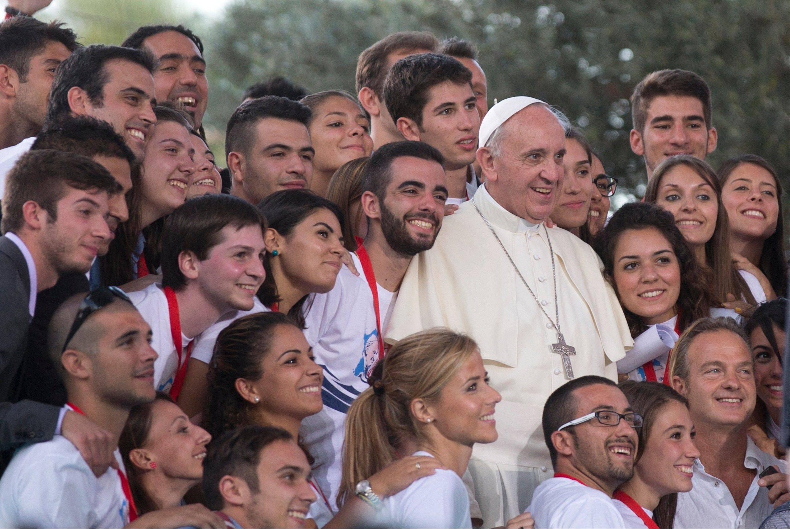 Pope Francis poses for a photo after a meeting with youths in downtown Cagliari, Italy, Sunday. Francis denounced what he called big business's idolatry of money over man as he traveled Sunday to one of Italy's poorest regions to offer hope to the unemployed and entrepreneurs struggling to hang on.