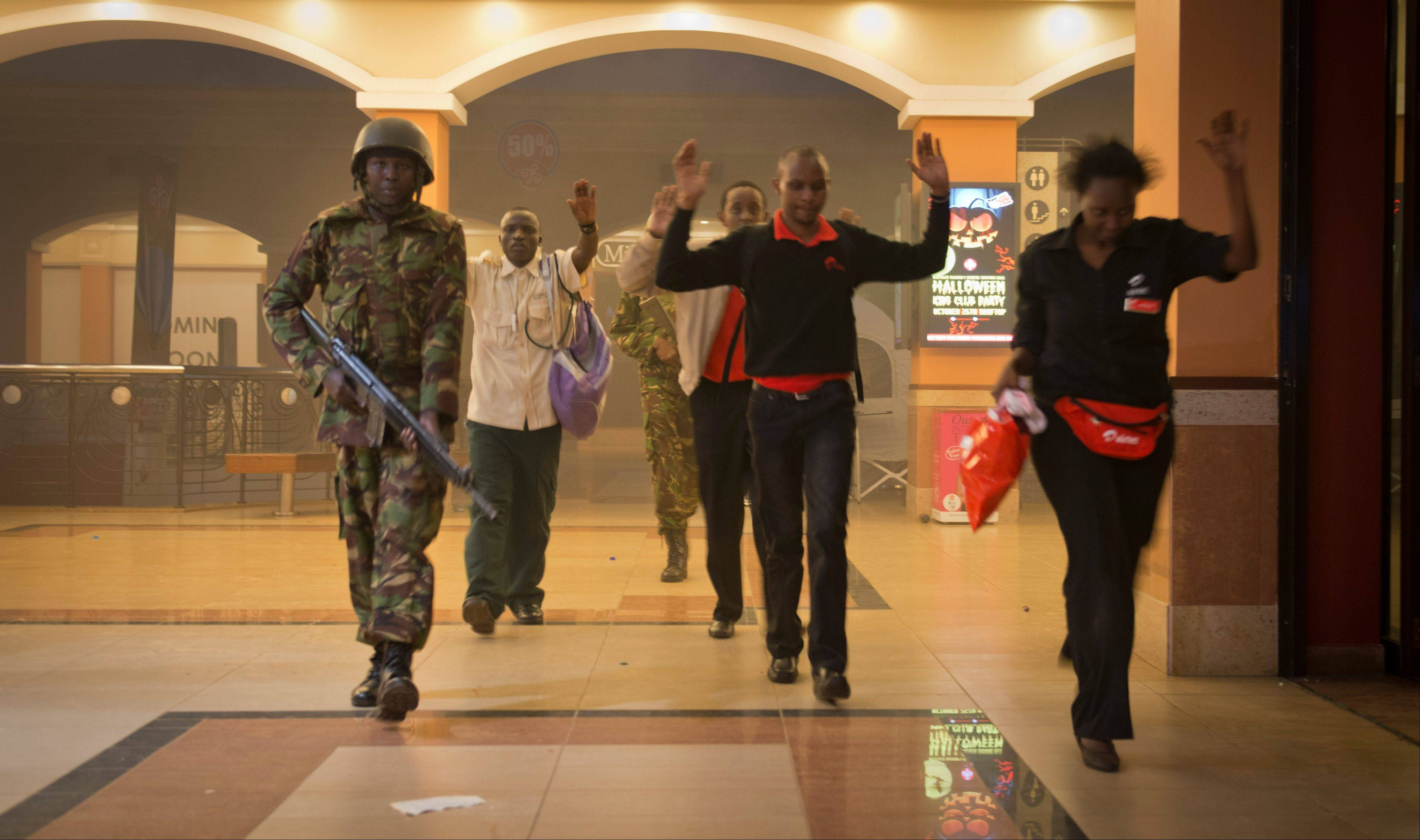 Civilians who had been hiding during the gun battle hold their hands in the air as a precautionary measure before being searched by armed police leading them to safety, inside the Westgate Mall in Nairobi, Kenya Saturday, Sept. 21, 2013. Gunmen threw grenades and opened fire Saturday, killing at least 22 people in an attack targeting non-Muslims at an upscale mall in Kenya's capital that was hosting a children's day event, a Red Cross official and witnesses said.