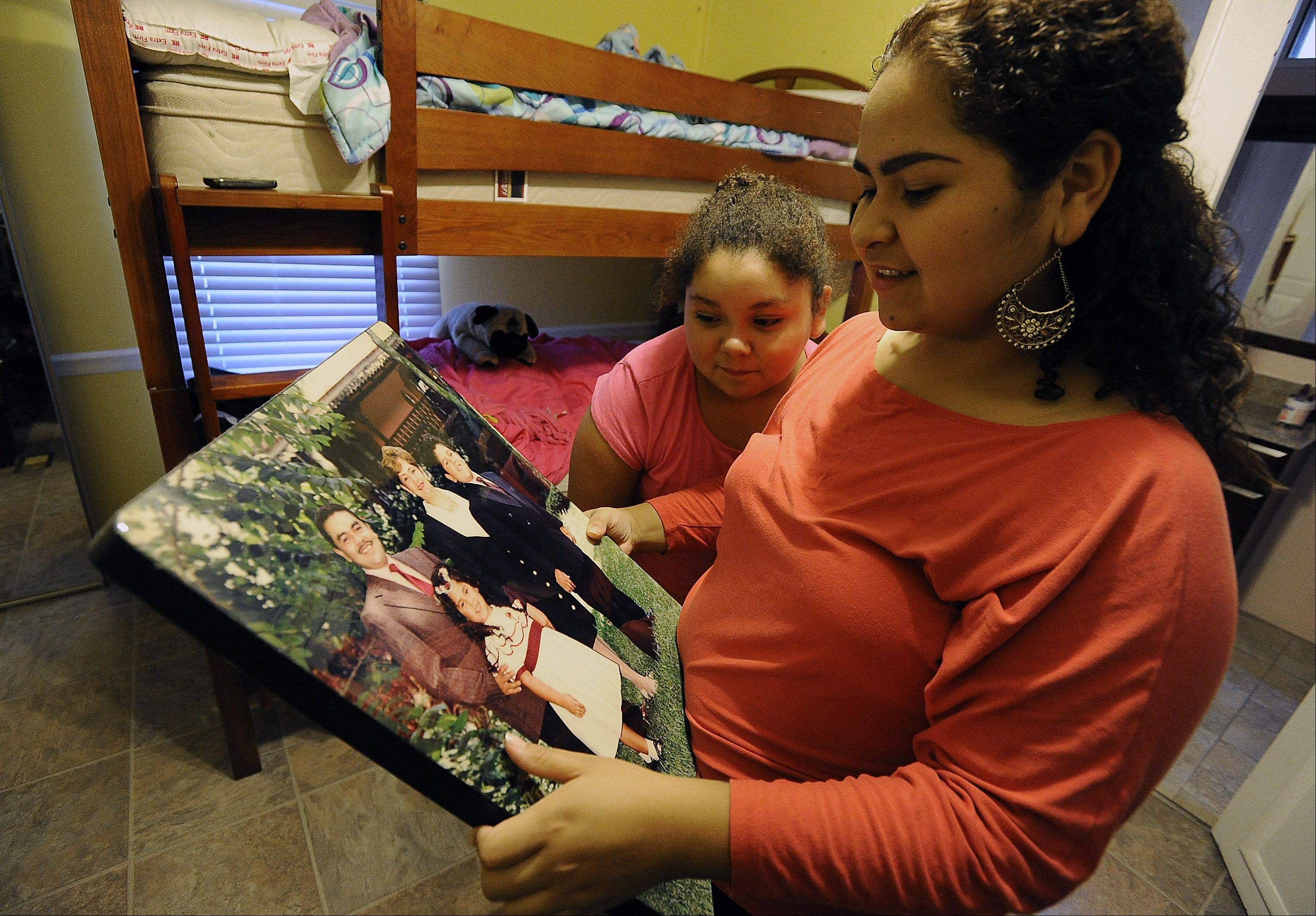 Greta Ramirez and her sister Karen look over a family picture from happier times in the bedroom they share in their Des Plaines area home.