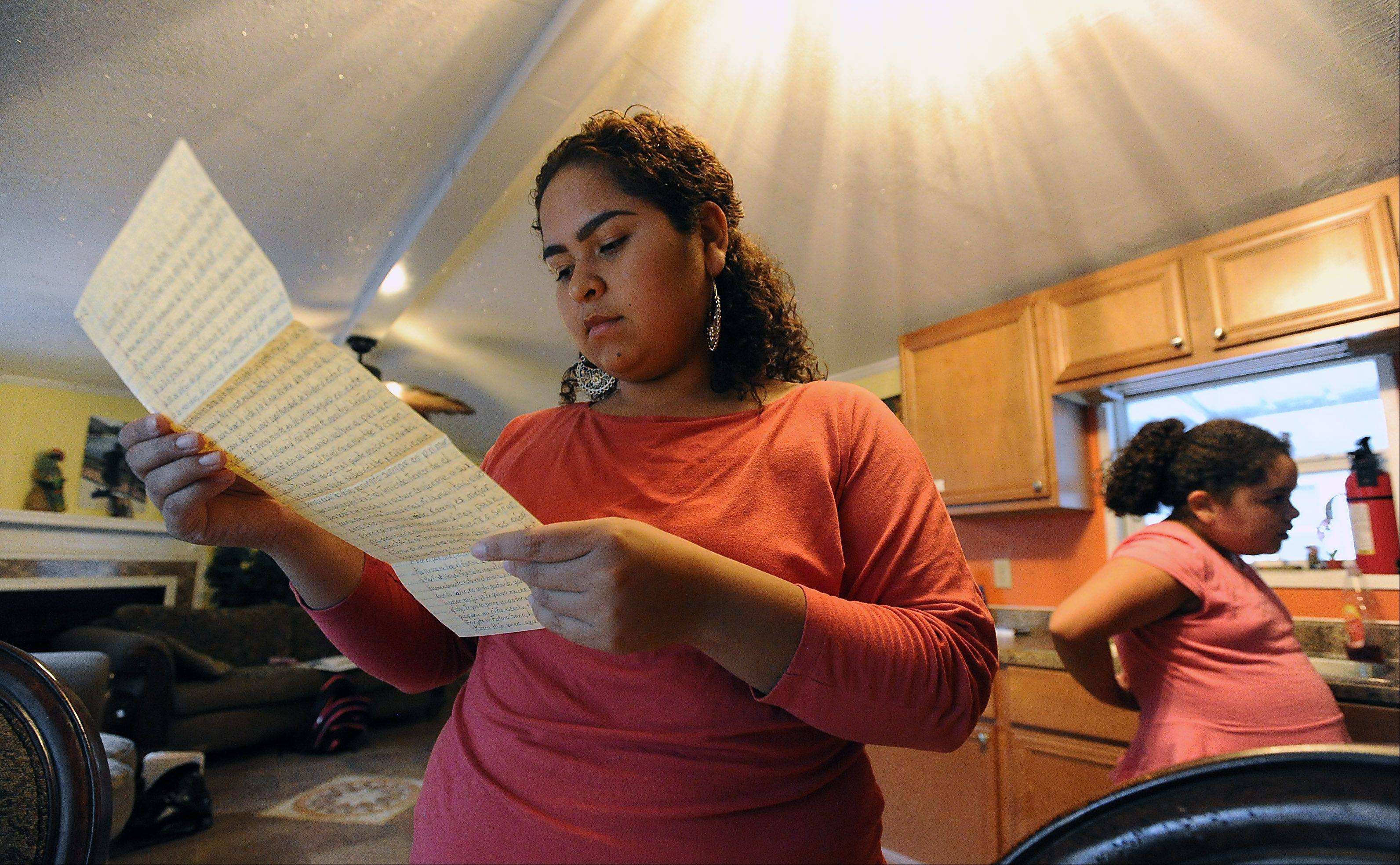 Karen Ramirez, 22, reads a letter from her father, Heriberto, who is in prison for killing their mother in 2011 in their Des Plaines-area home while Greta, 12, sat nearby.