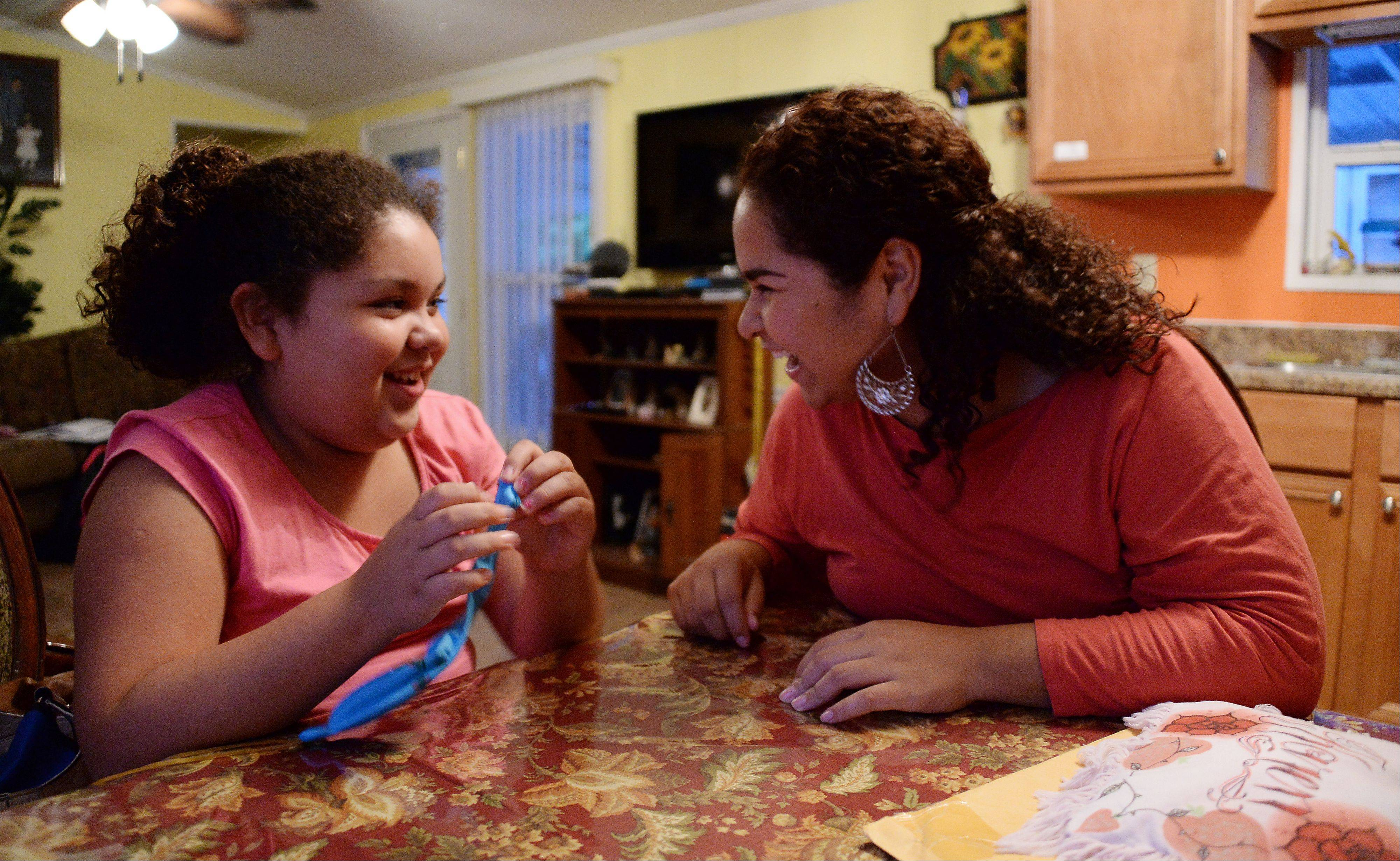 Greta, 12, left, and her sister Karen Ramirez, 22, who live near Des Plaines, share a laugh together at their dining room table as they talk about good times with their mother, Alicia.