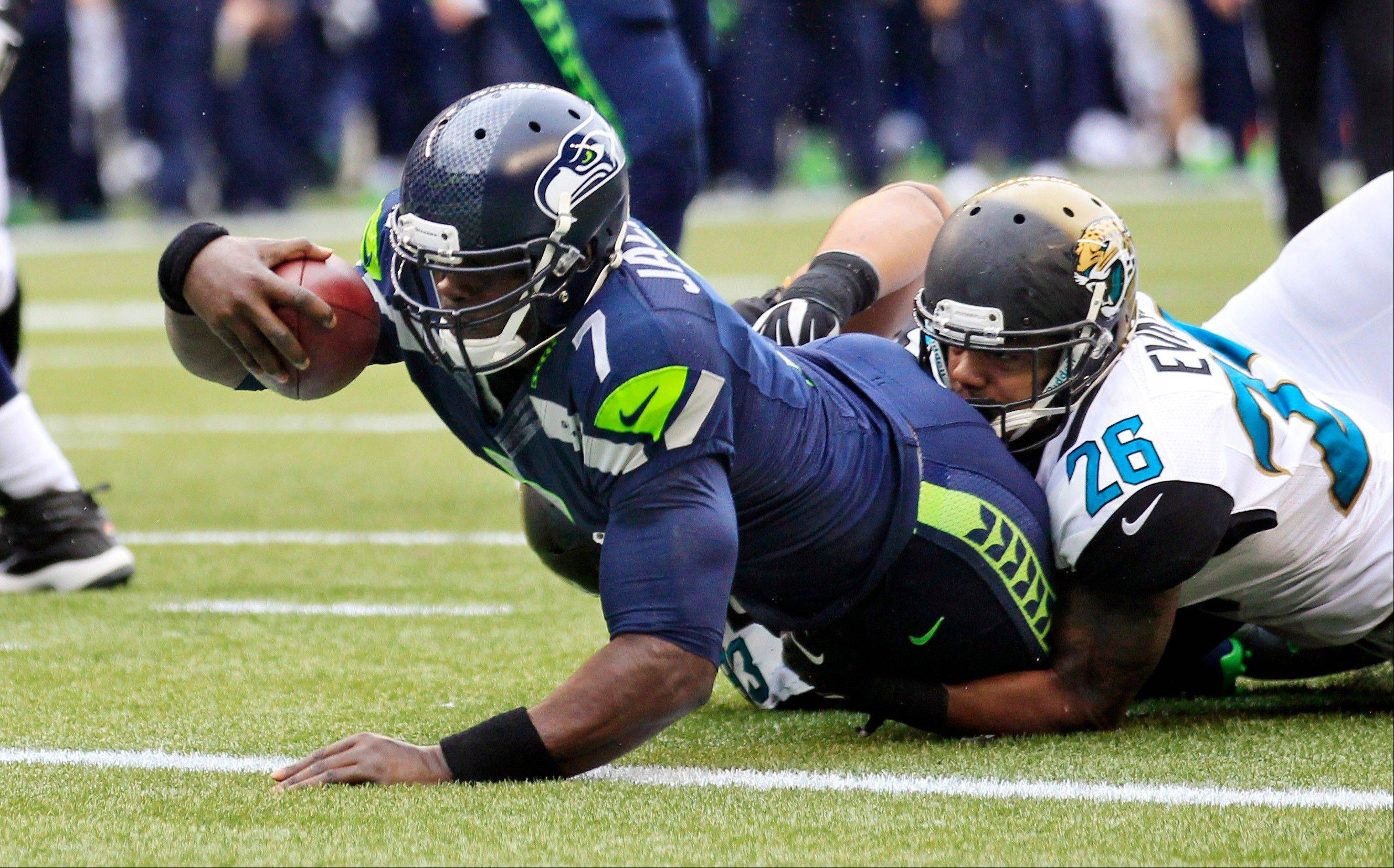 Seattle Seahawks backup quarterback Tarvaris Jackson (7) scores on a keeper as Jacksonville Jaguars' Josh Evans brings him down in the second half of an NFL football game on Sunday, Sept. 22, 2013, in Seattle.