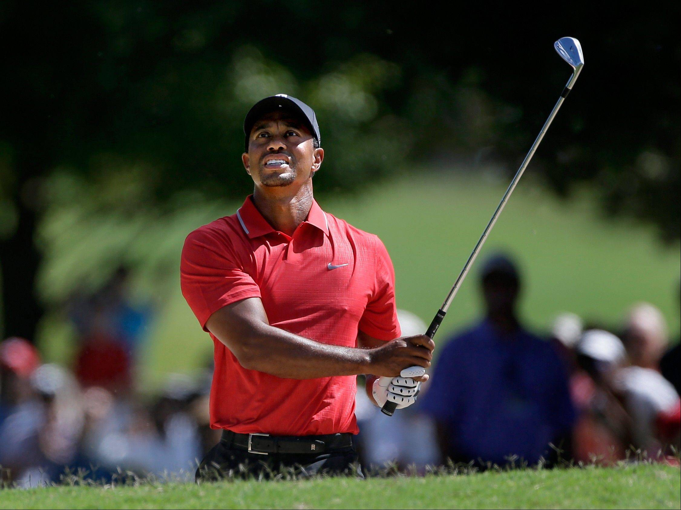 Tiger Woods hits out of the bunker on the third hole during the final round of play in the Tour Championship golf tournament at East Lake Golf Club, in Atlanta, Sunday, Sept. 22, 2013.