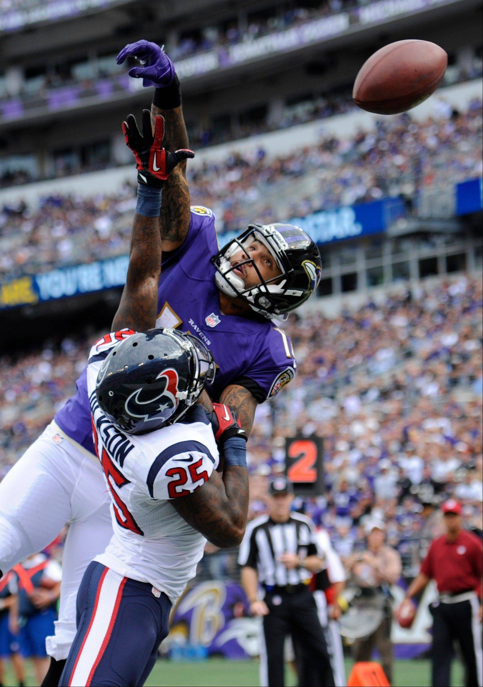 Houston Texans cornerback Kareem Jackson, bottom, breaks up a pass attempt to Baltimore Ravens wide receiver Tandon Doss in the second half of an NFL football game Sunday, Sept. 22, 2013, in Baltimore. Houston received a defensive pass interference call on the play.