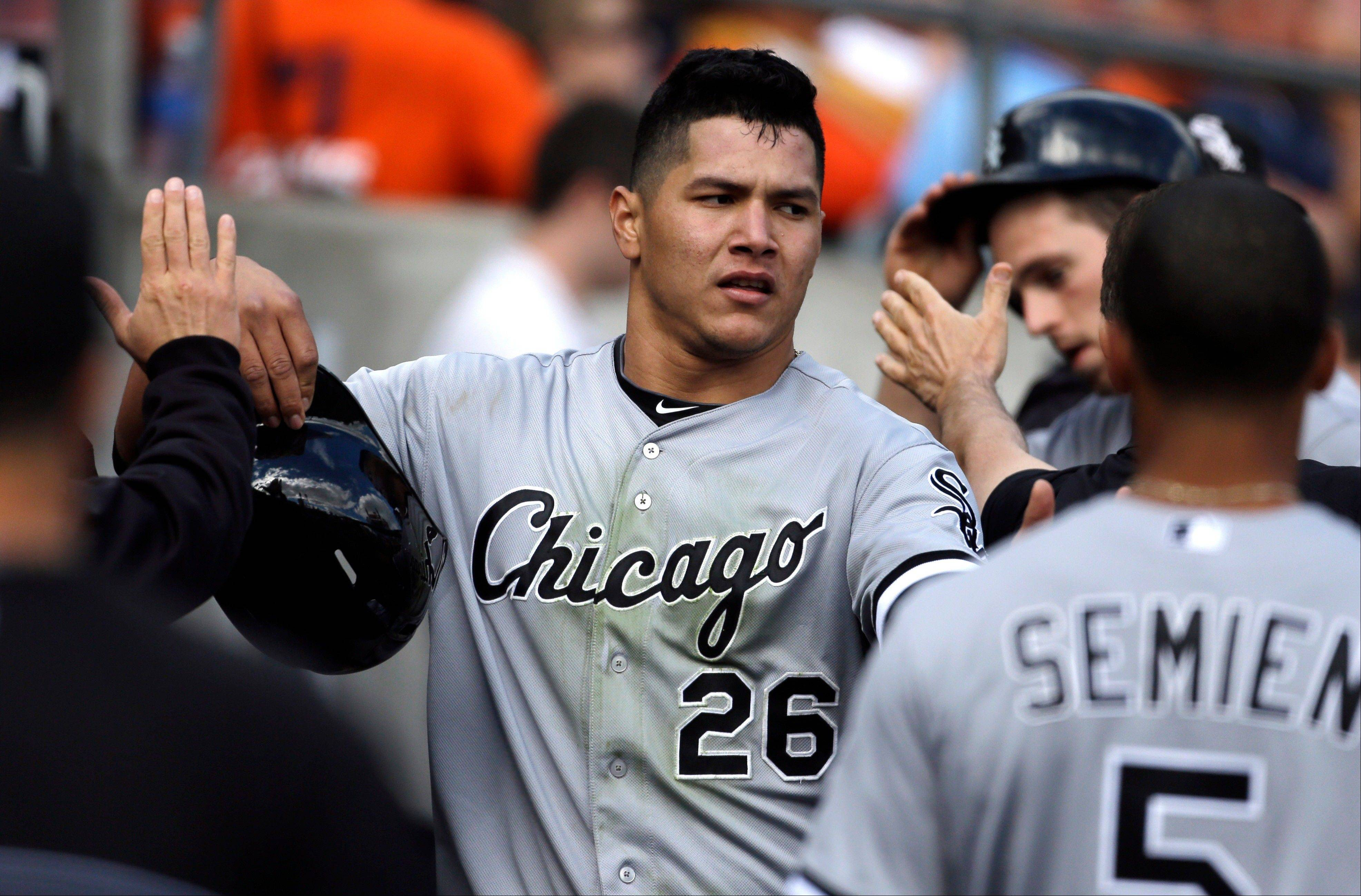 White Sox right fielder Avisail Garcia (26) is congratulated in the dugout after scoring on a two-run double hit by teammate Jeff Keppinger during the seventh inning of a baseball game against the Detroit Tigers in Detroit, Sunday, Sept. 22, 2013.