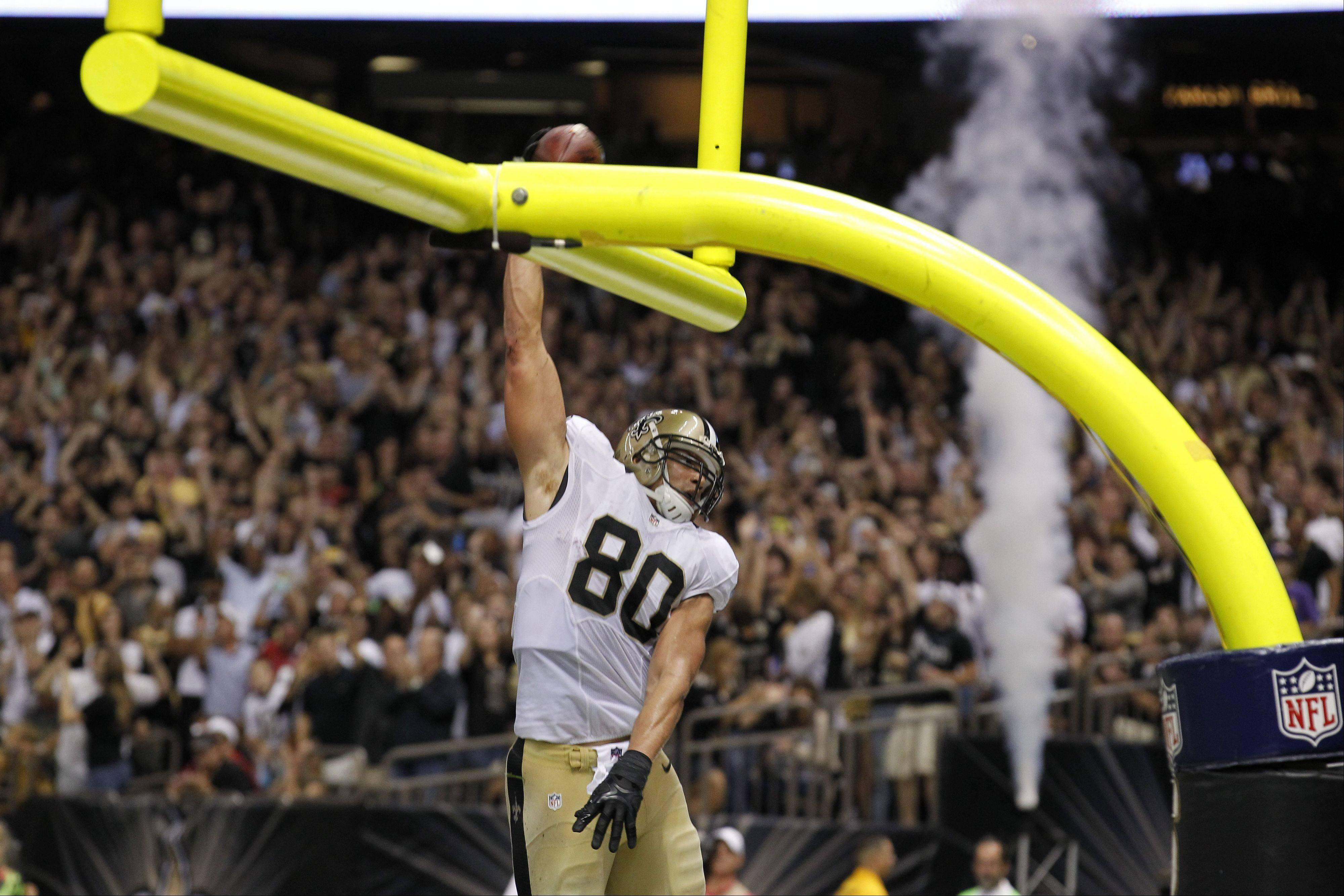 New Orleans Saints tight end Jimmy Graham (80) slam dunks over the goalpost after scoring on a touchdown reception in the second half of an NFL football game against the Arizona Cardinals in New Orleans, Sunday, Sept. 22, 2013.
