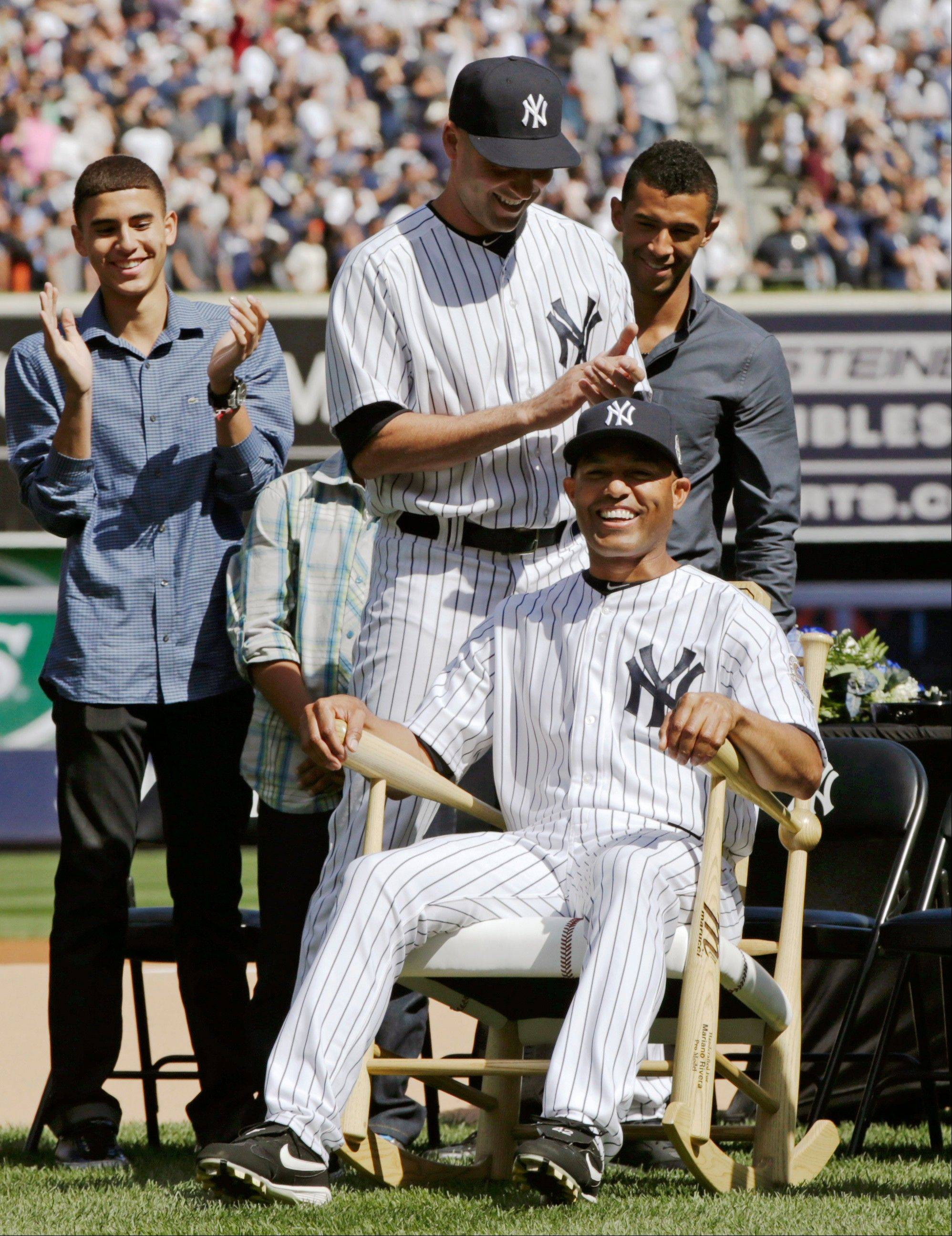 New York Yankees Derek Jeter, standing center, applauds as Yankees relief pitcher Mariano Rivera (42) tries out a rocking chair, one of many gifts Rivera received during a pregame retirement ceremony at Yankee Stadium before the Yankees baseball game against the San Francisco Giants, Sunday, Sept. 22, 2013, in New York. Rivera's sons Jafet, left, and Mariano Jr. watch the action. The 13-time All-Star closer is retiring at the end of this season.