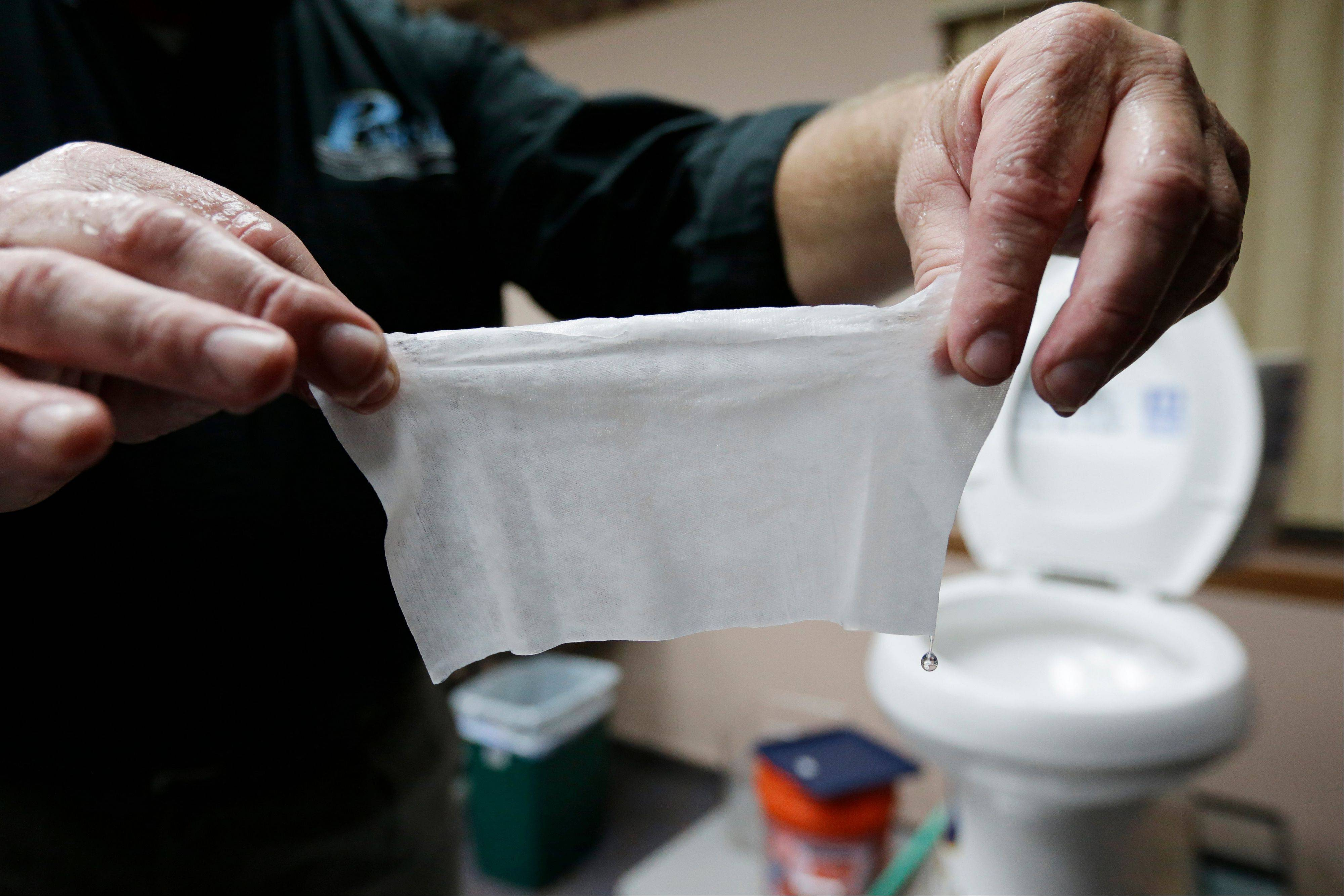Rob Villee, executive director of the Plainfield Area Regional Sewer Authority in New Jersey, holds up a wipe he flushed through his test toilet in his office. Increasingly popular bathroom wipes, thick, premoistened towelettes that are advertised as flushable, are creating clogs and backups in sewer systems around the nation.