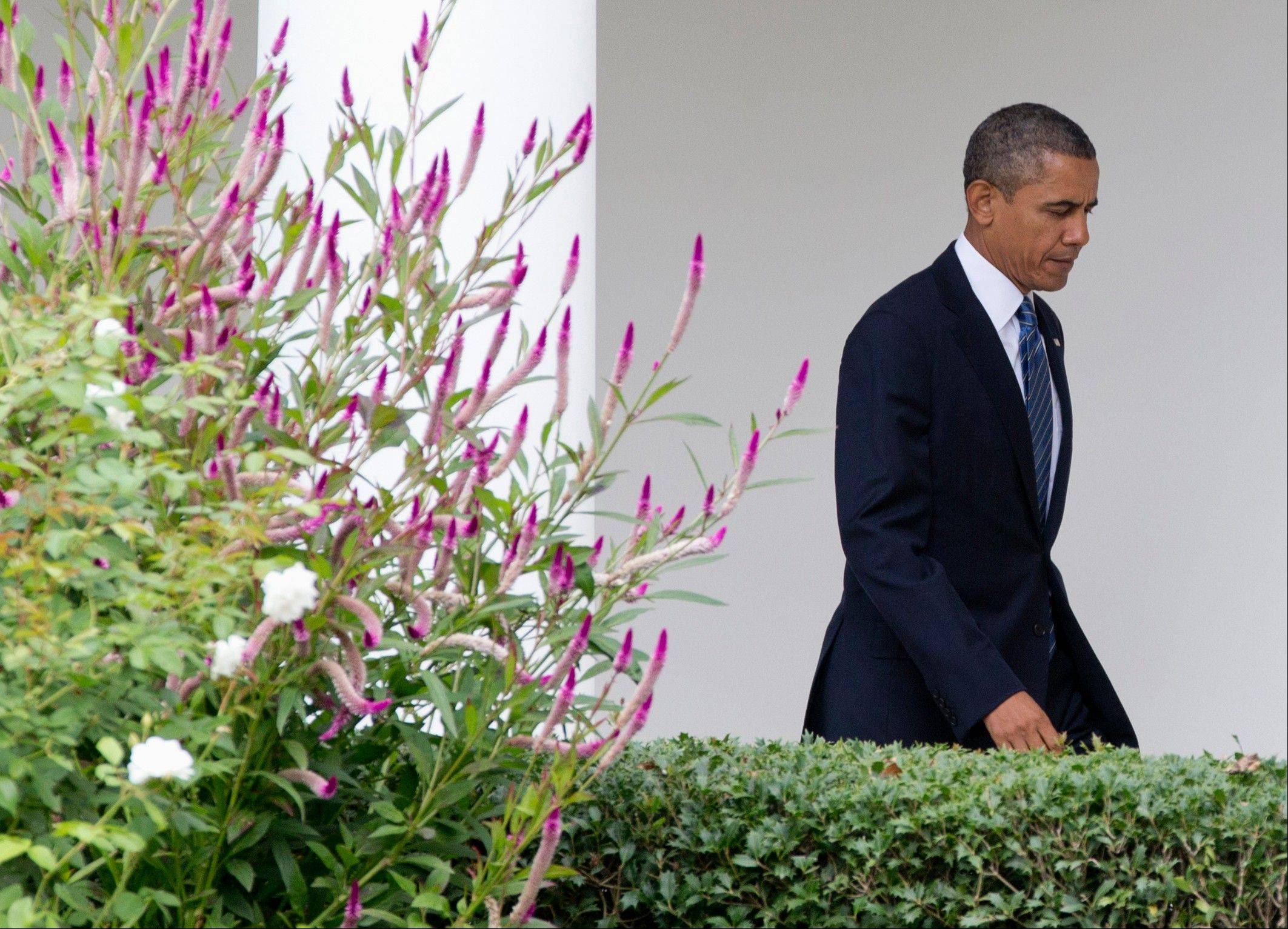 President Barack Obama walks from the Oval Office of the White House in Washington along the colonnade to join first lady Michelle Obama as they travel Monday to the United Nations General Assembly in New York.