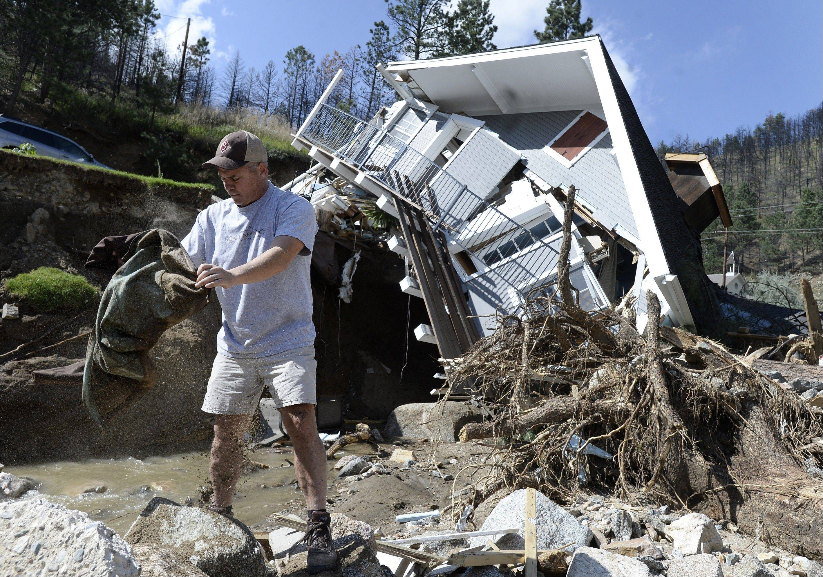 Sean McCroskey pulls his wife Meg's jacket out of the debris in the river in front of their destroyed home on Gold Run Road in Boulder County, Colo. State highway crews and National Guard troops worked Sunday.