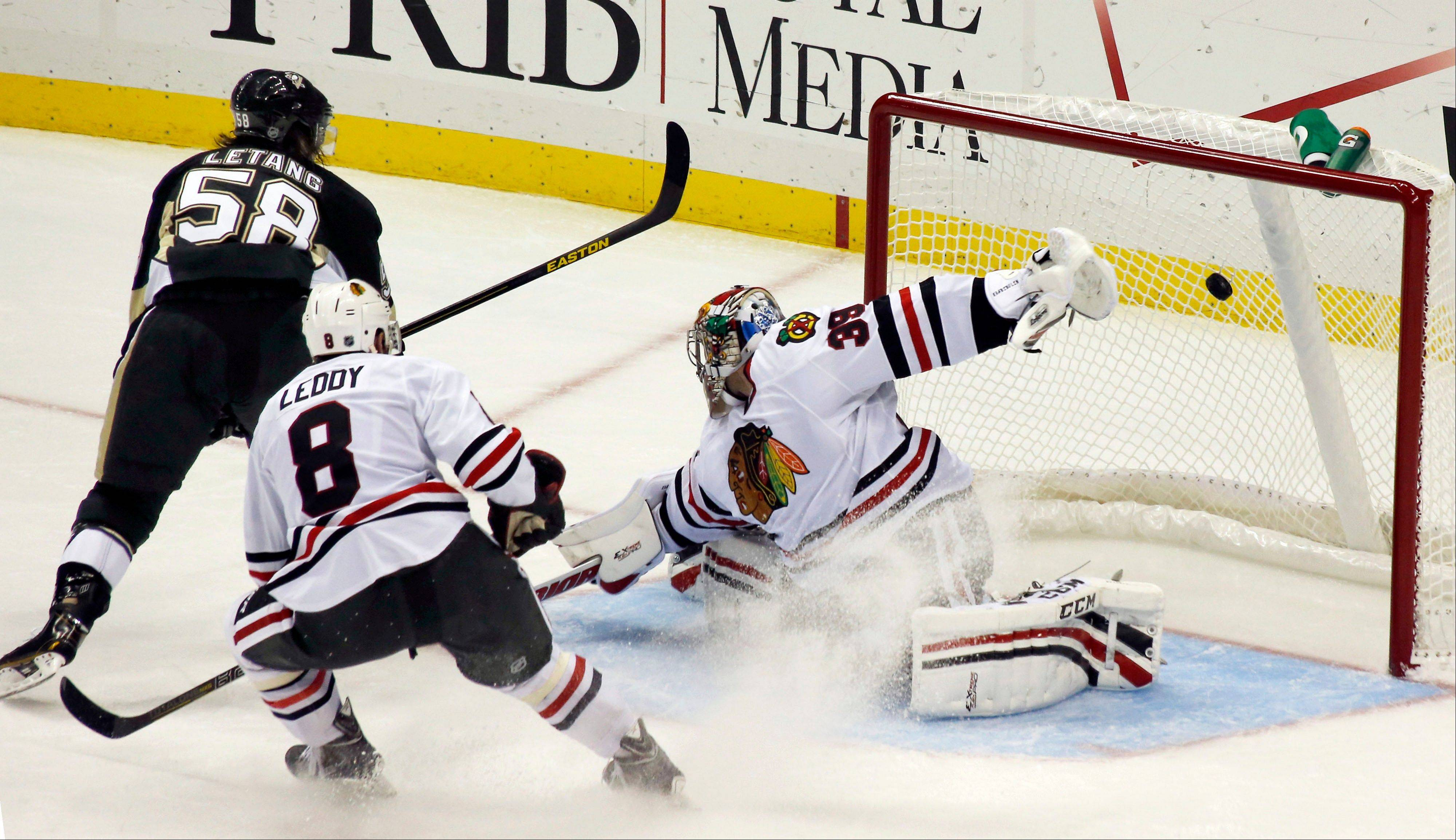 The Penguins' Kris Letang scores the first of his 2 goals on Blackhawks goalie Nikolai Khabibulin in the third period Monday night.