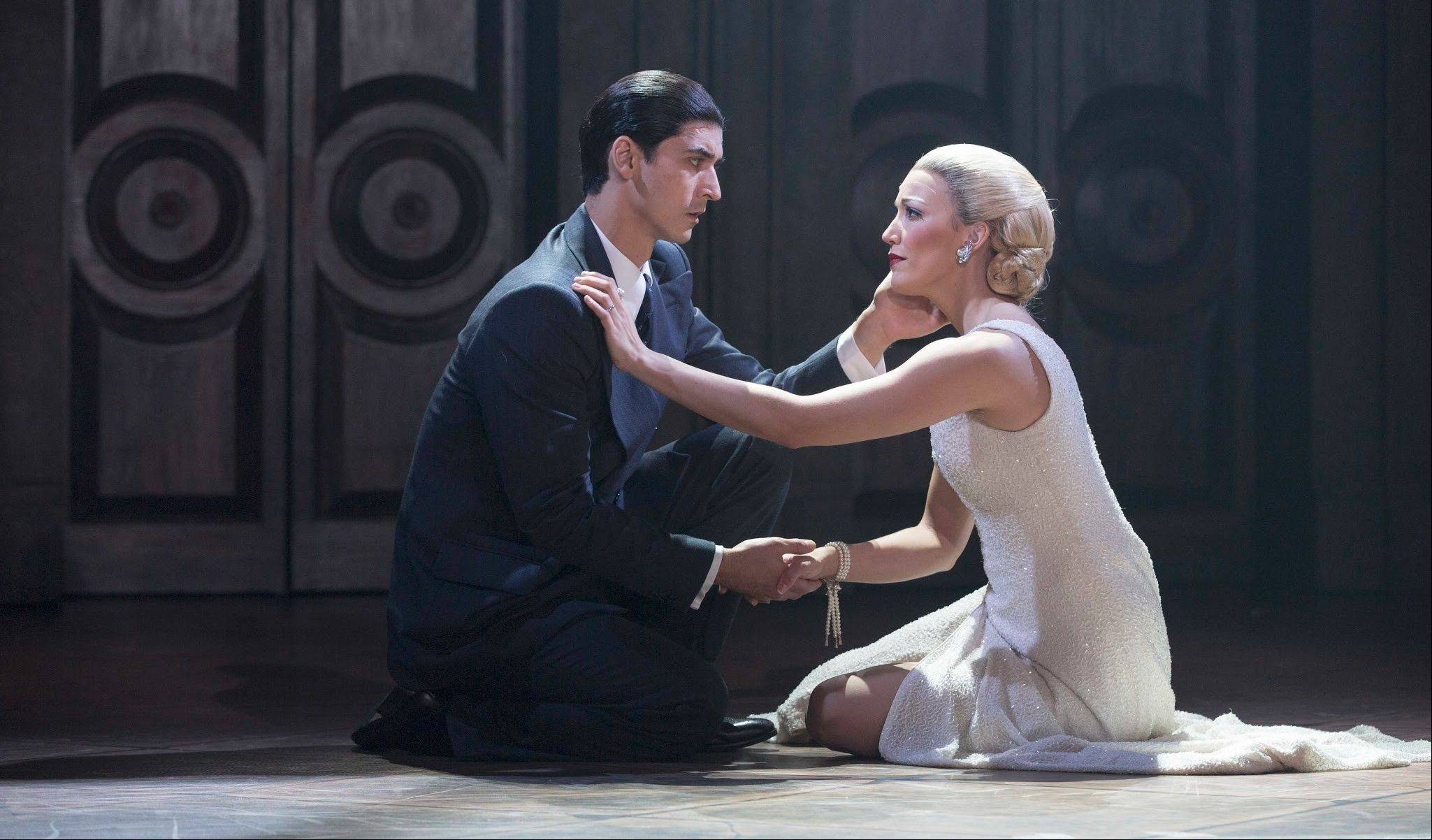 "Juan Peron (Sean MacLaughlin) comforts his ill wife, Eva Peron (Caroline Bowman), as she sings the interpolated 1996 film song ""You Must Love Me"" in the national tour of ""Evita."" The musical continues at the Oriental Theatre in Chicago through Oct. 6."