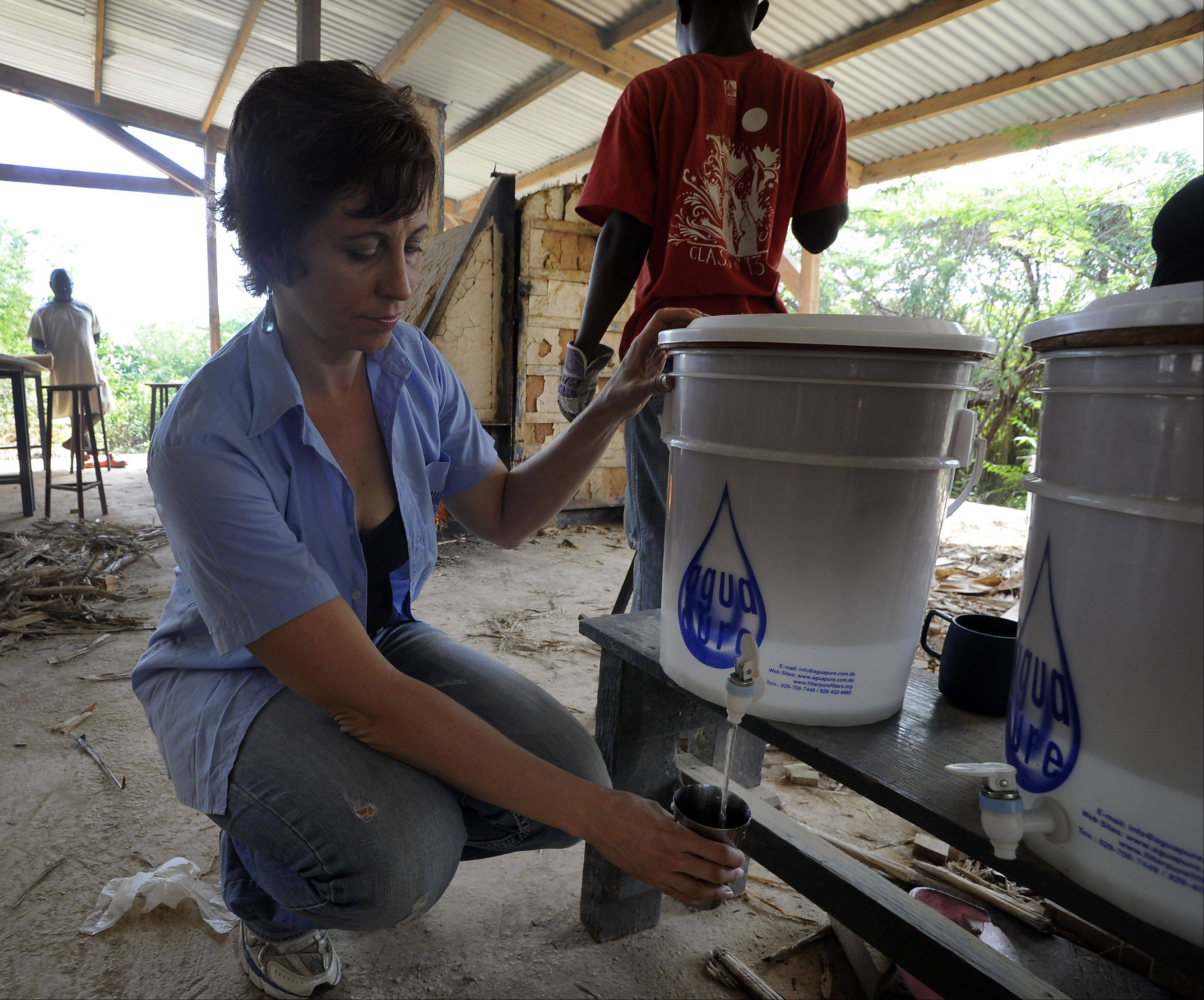 Lisa Ballantine, director of FilterPure, takes a drink from one of her charity's water filters in a factory in Jacmel, Haiti, as workers fire more filters in the kiln behind her.