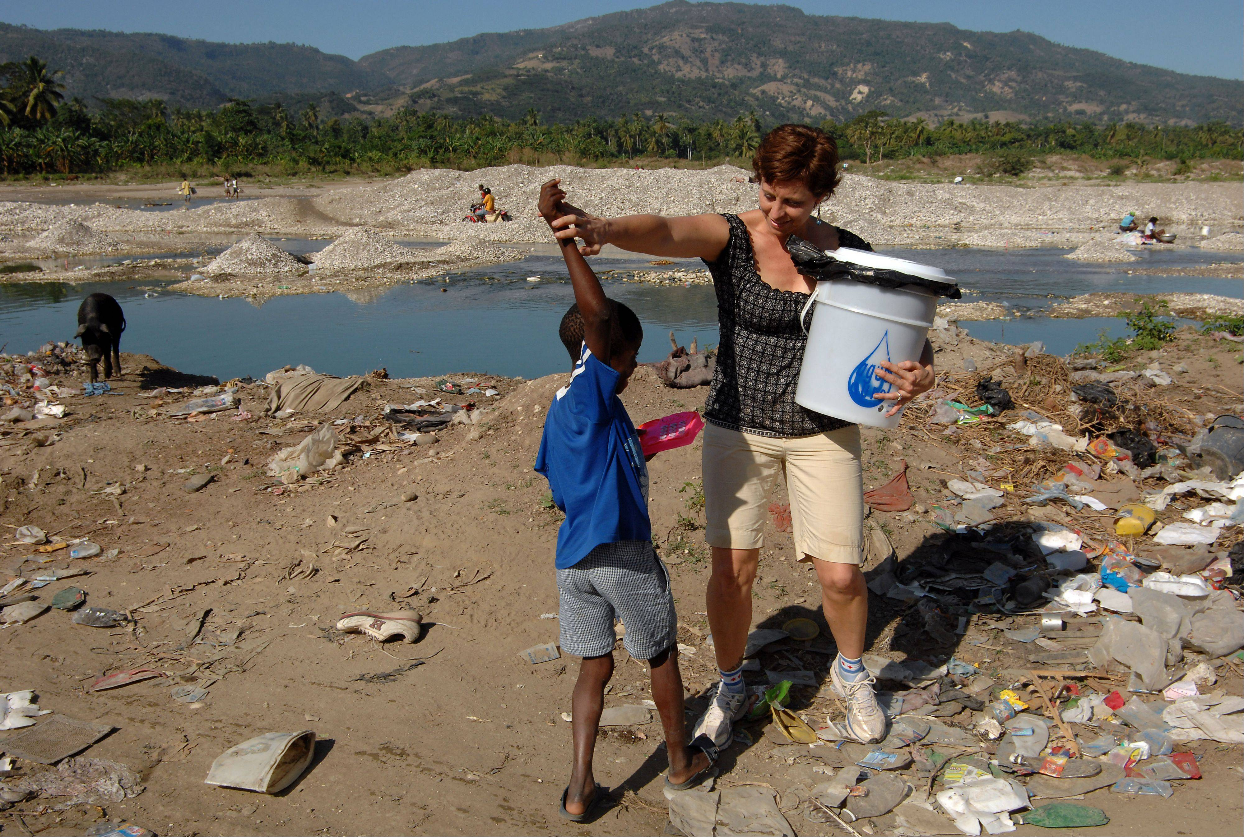 FilterPure Director Lisa Ballantine, formerly of Elk Grove Village, dances with a boy in the dump area of Jacmel, Haiti, as she walked to find houses that were using her water filter.