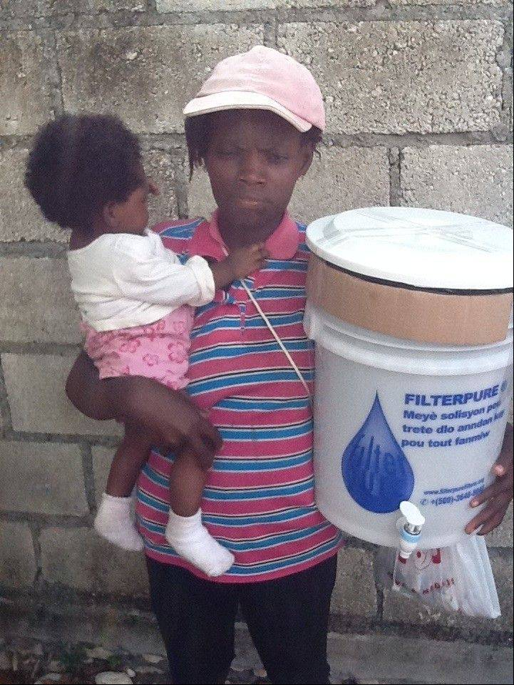 A woman in Haiti holds a FilterPure water filter, which helps them have clean drinking water. The filters are created by a charity run by former Elk Grove Village resident Lisa Ballantine.