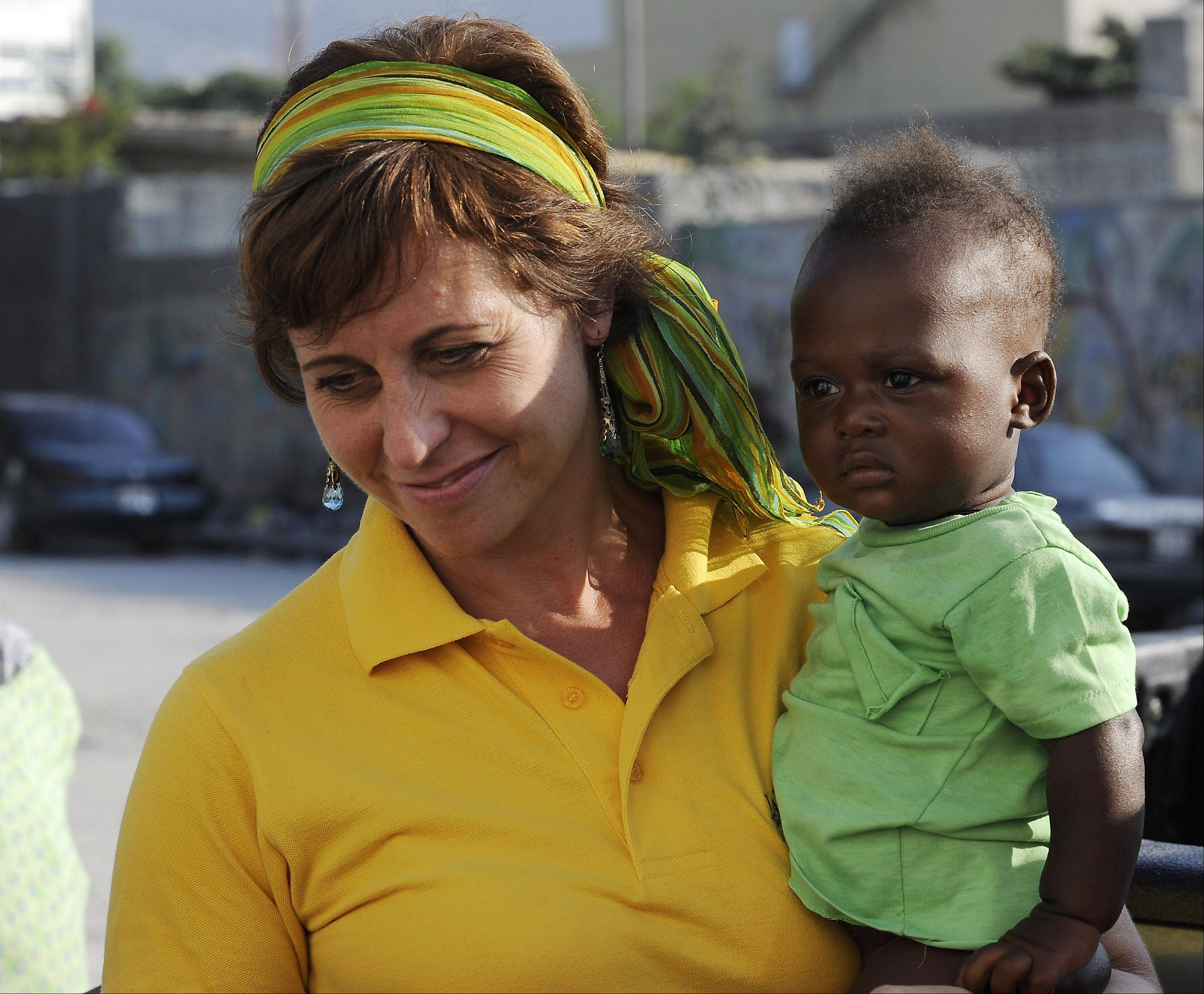 FilterPure Director Lisa Ballantine, formerly of Elk Grove Village, poses with a Haitian child in Port-au-Prince. Ballantine's charity provides sustainable water filters to help people in Haiti and the Dominican Republic have clean drinking water.