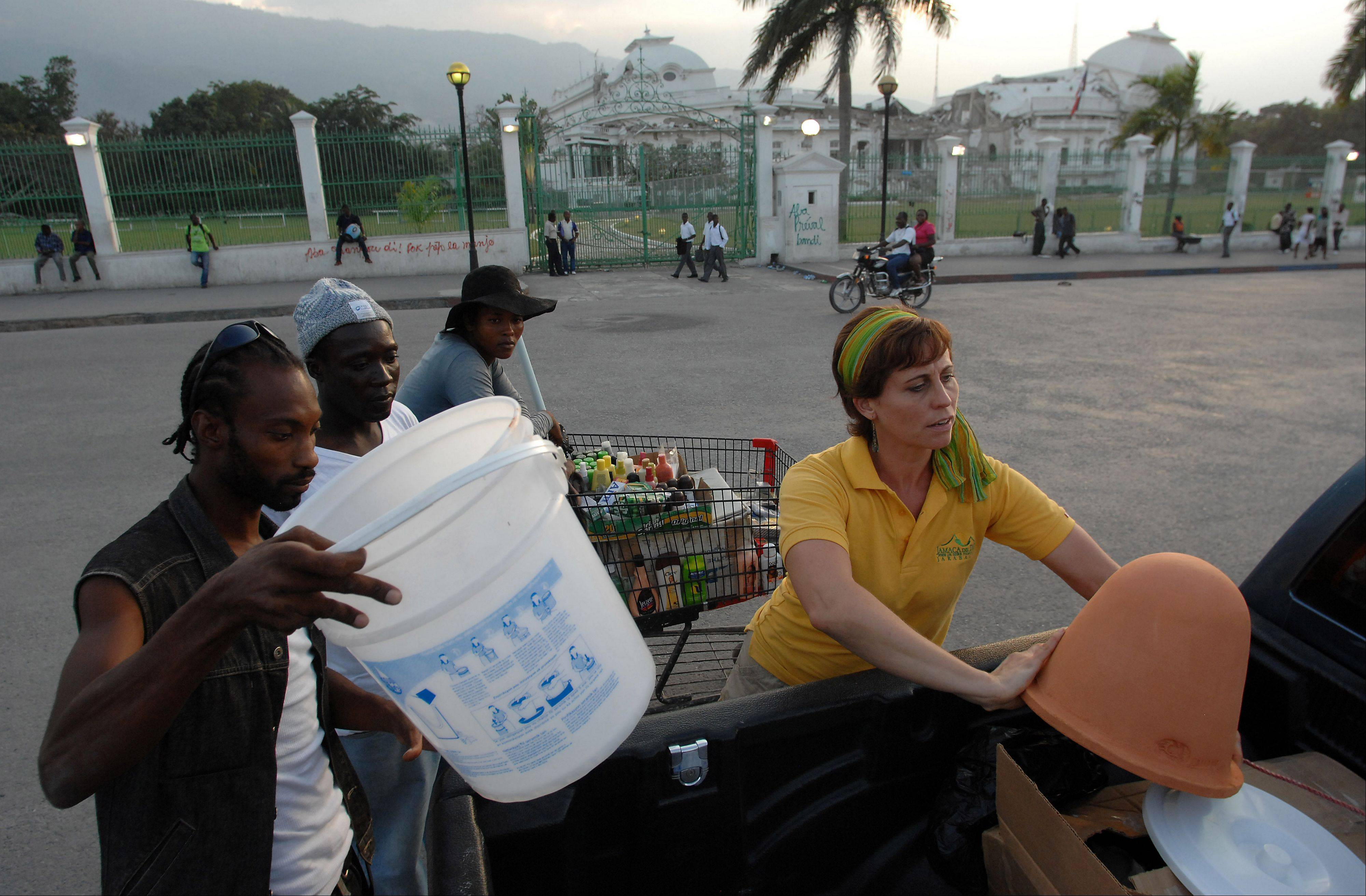 FilterPure Director Lisa Ballantine, formerly of Elk Grove Village, shows off a water filter to Haitians in a tent city in Port-au-Prince.