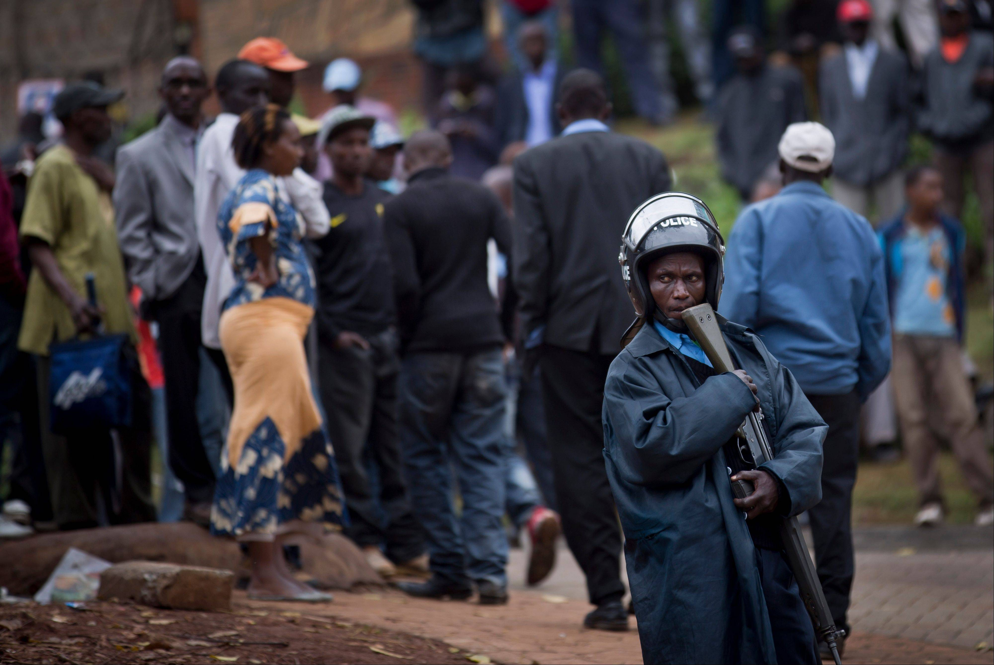 A Kenyan policeman keeps crowds of onlookers back from the Westgate Mall, in Nairobi, Kenya Monday, Sept. 23, 2013. Four large blasts rocked Kenya's Westgate Mall on Monday, sending large plumes of smoke over an upscale suburb as Kenyan military forces sought to rescue an unknown number of hostages held by al-Qaida-linked militants.