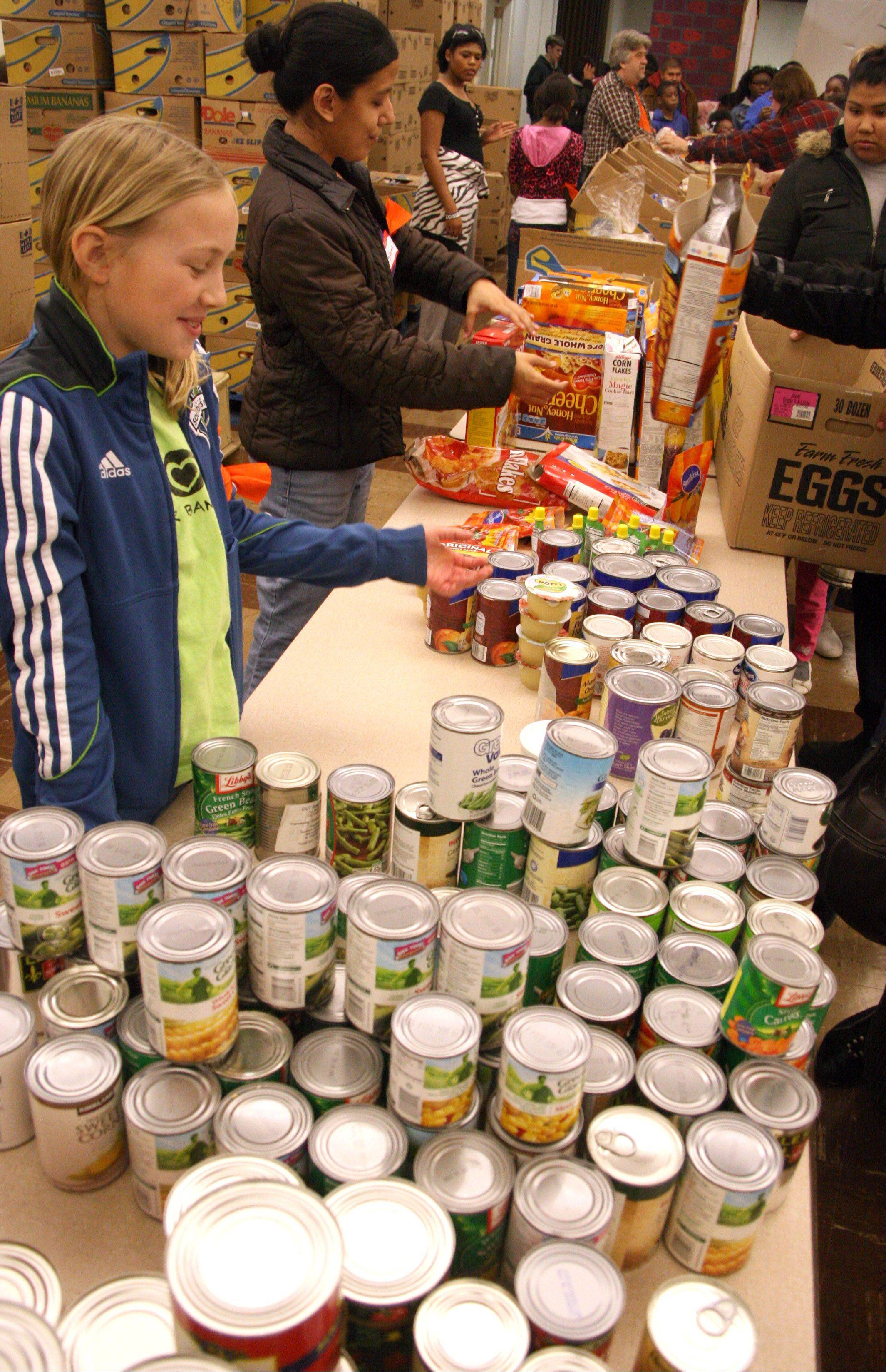 Rachel Lawrence, 11, left, of Geneva and Magdalena Plazola of Elgin, center, volunteer their services offering canned food at the First United Methodist Church as part of last year's Love Elgin Day event.